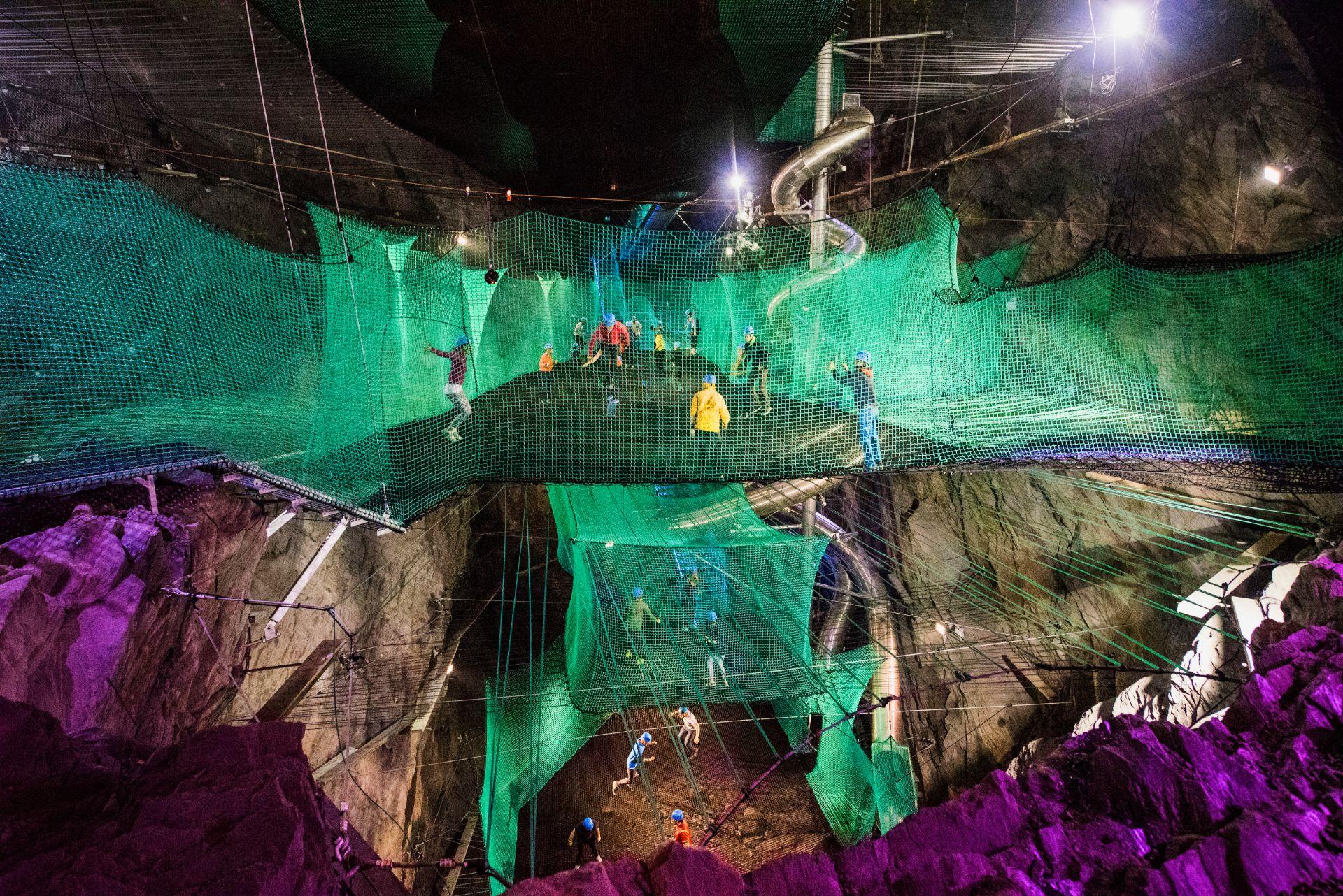people-bouncing-on-netted-underground-trampolines-in-cavern-bounce-below-zip-world-snowdonia-outdoor-activities-wales