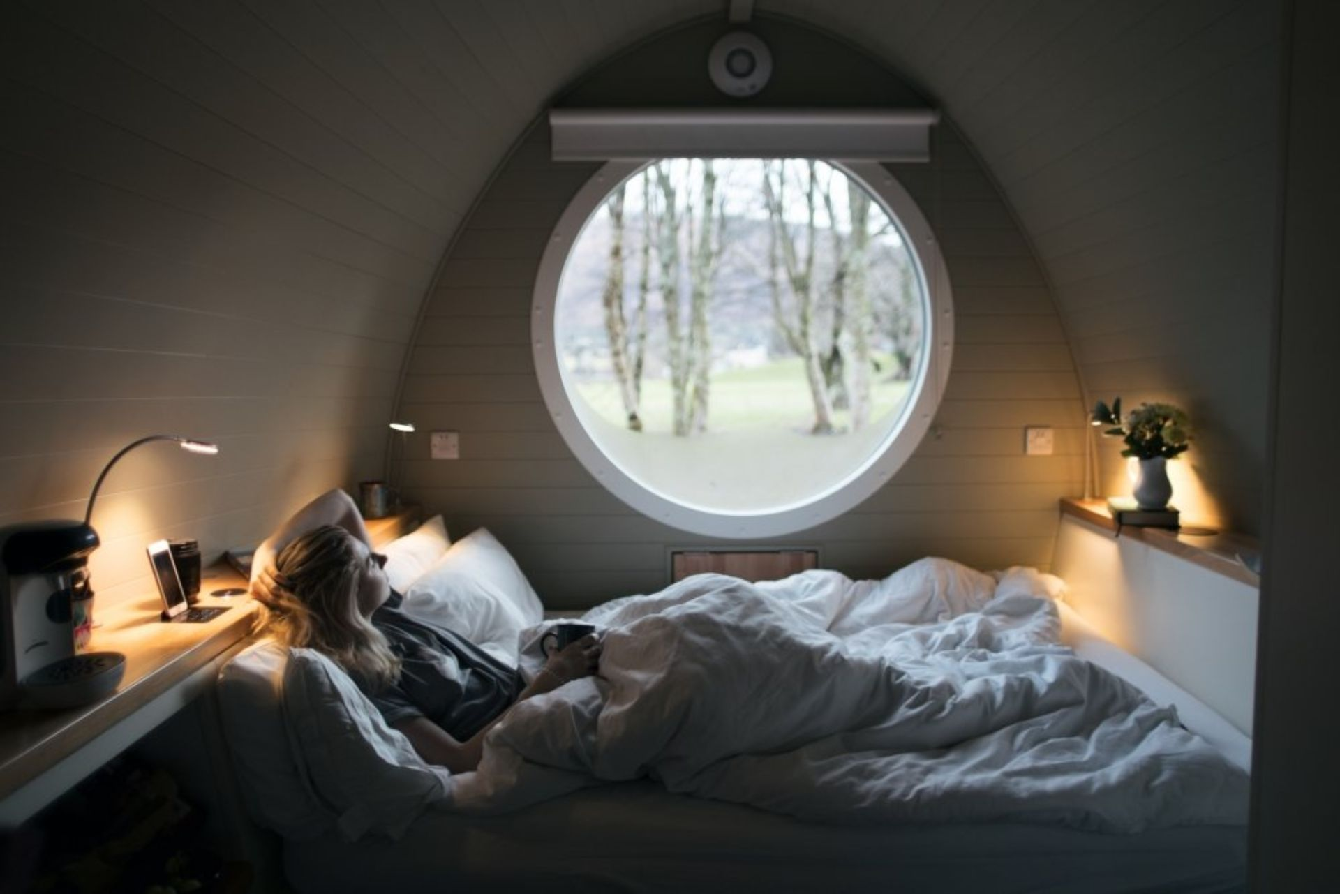 blonde-woman-lying-in-bed-in-glamping-pod-looking-out-of-a-round-window-riverbeds-lodge-glencoe-glamping-with-hot-tub-in-scotland