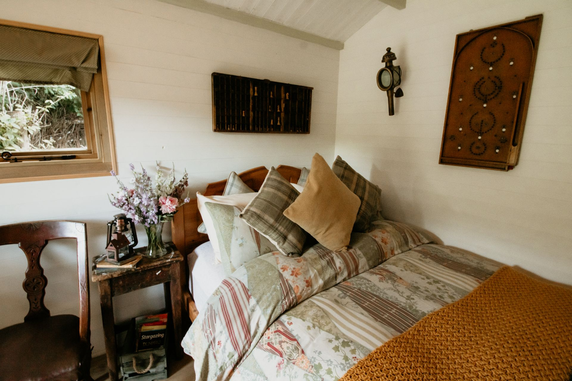 bed-covered-in-cosy-quilts-and-cushions-in-prothero-shepherds-hut-the-moon-and-i-glamping-with-hot-tub-herefordshire