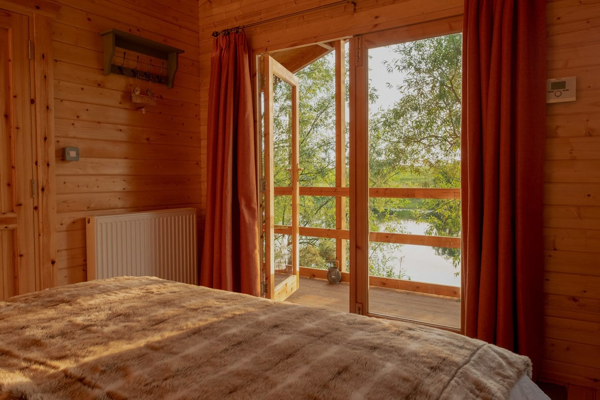 inside-of-a-wooden-cabin-bedroom-looking-out-to-balcony-and-lake-kingfisher-lake-cabins-driffield