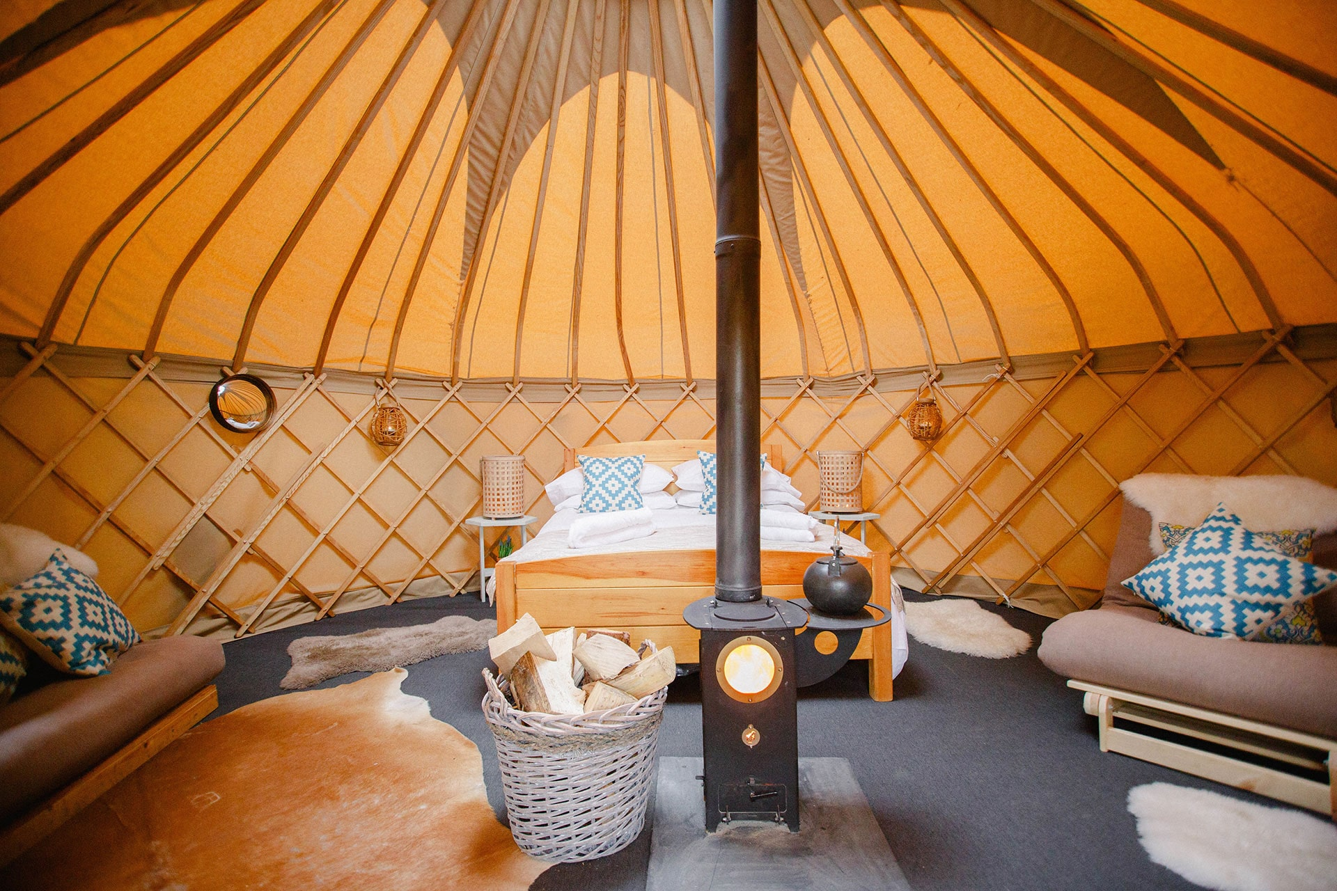 inside-of-cosy-yurt-with-bed-log-burner-and-sofas-yurtshire-fountains-yurts-ripon