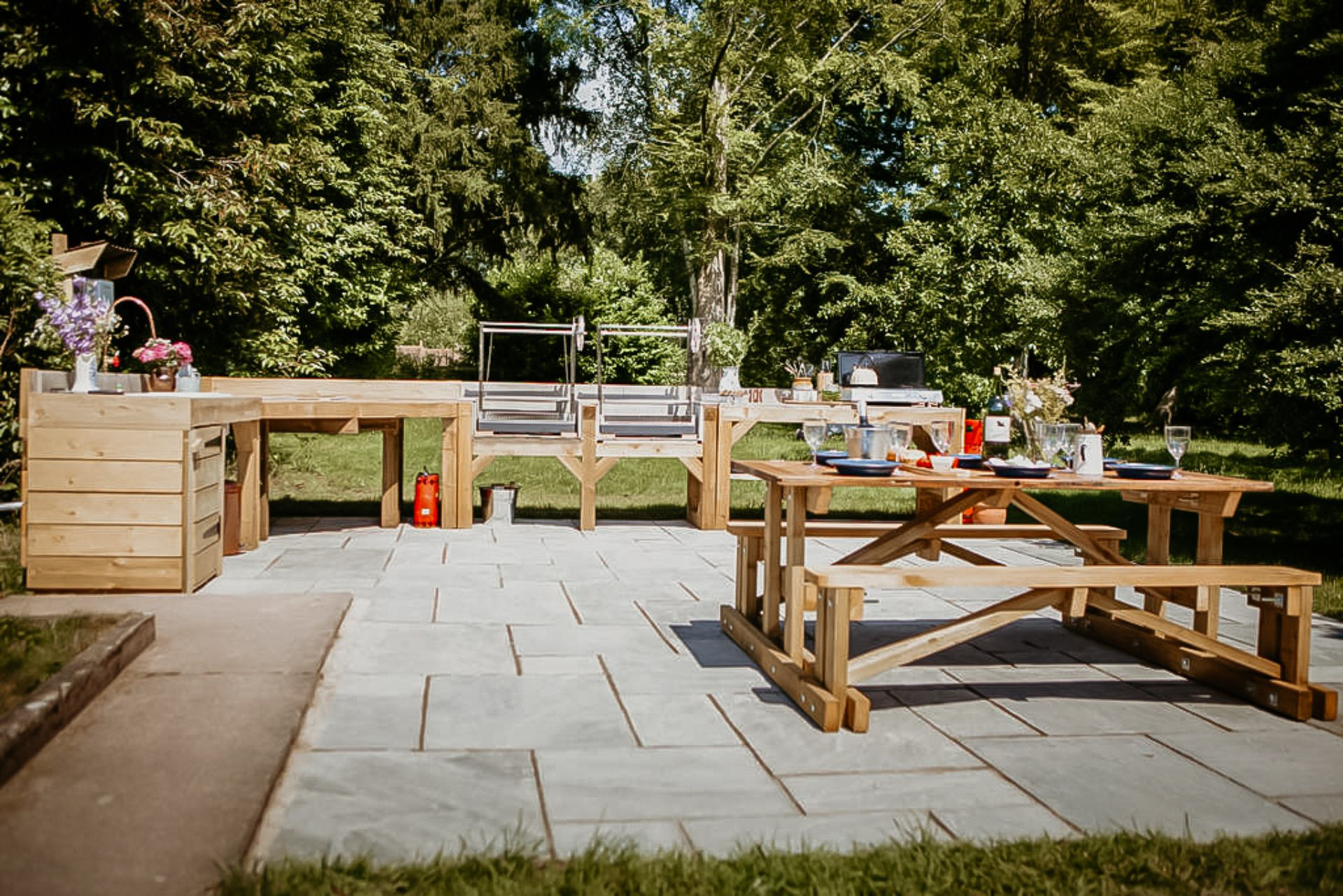 outdoor-communal-kitchen-area-with-picnic-table-and-benches-in-garden