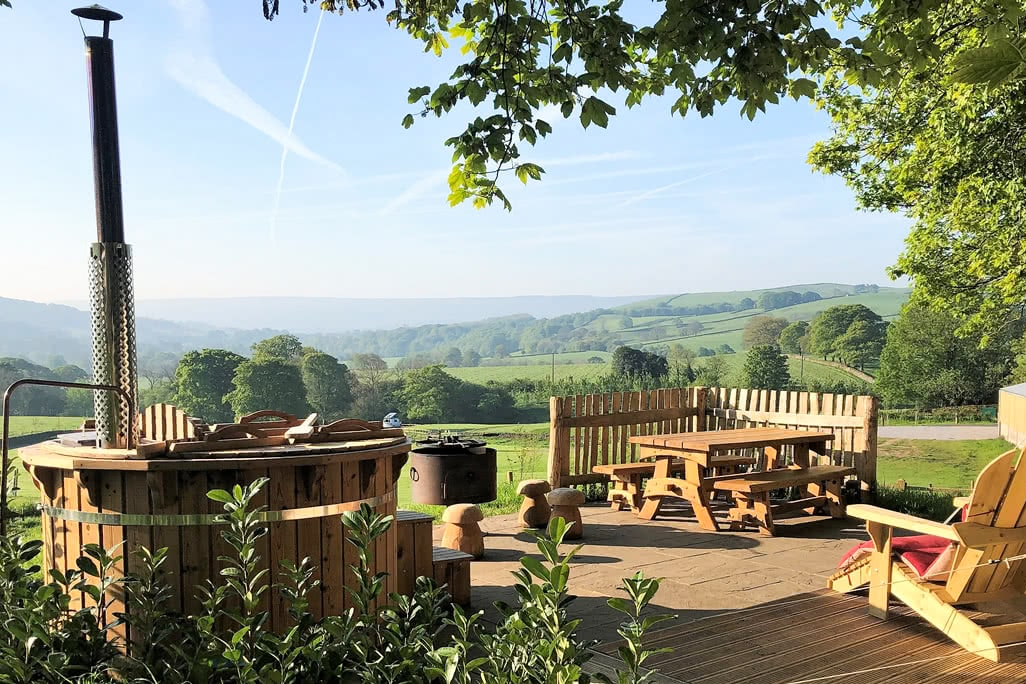 view-from-yurt-of-hot-tub-and-table-and-chairs-on-decking-in-countryside-fields-cat-gill-farm-glamping-bell-tents-skipton