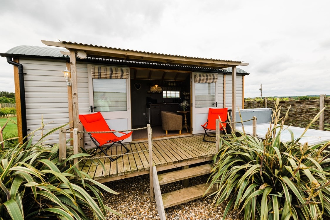 west-hale-gate-shepherds-hut-driffield-hut-on-a-wooden-platform-witha-hot-tub-and-deck-chairs-on-the-deck-glamping-with-hot-tub-yorkshire