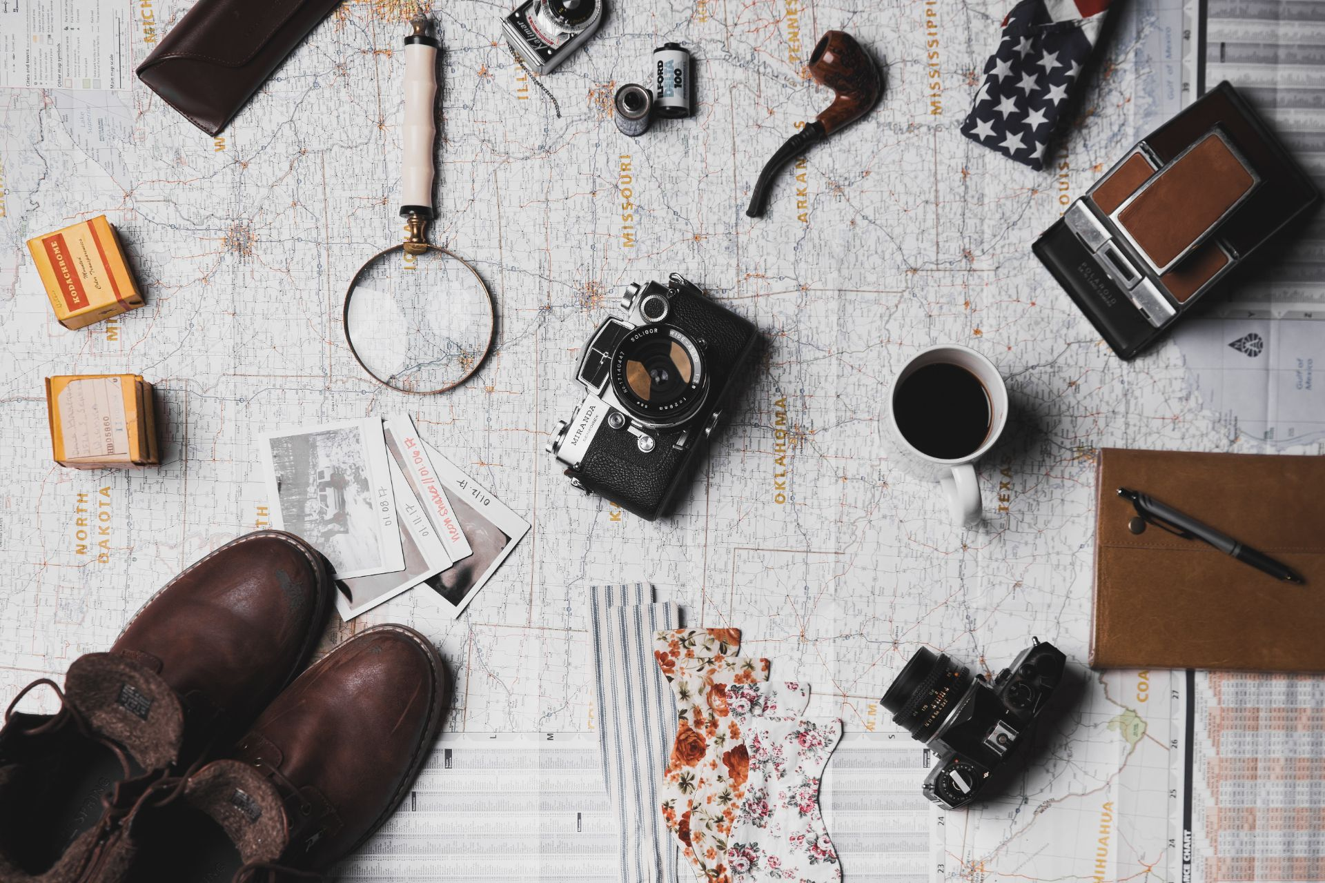 travel-planning-items-on-map-magnifying-glass-camera-notebook-boots