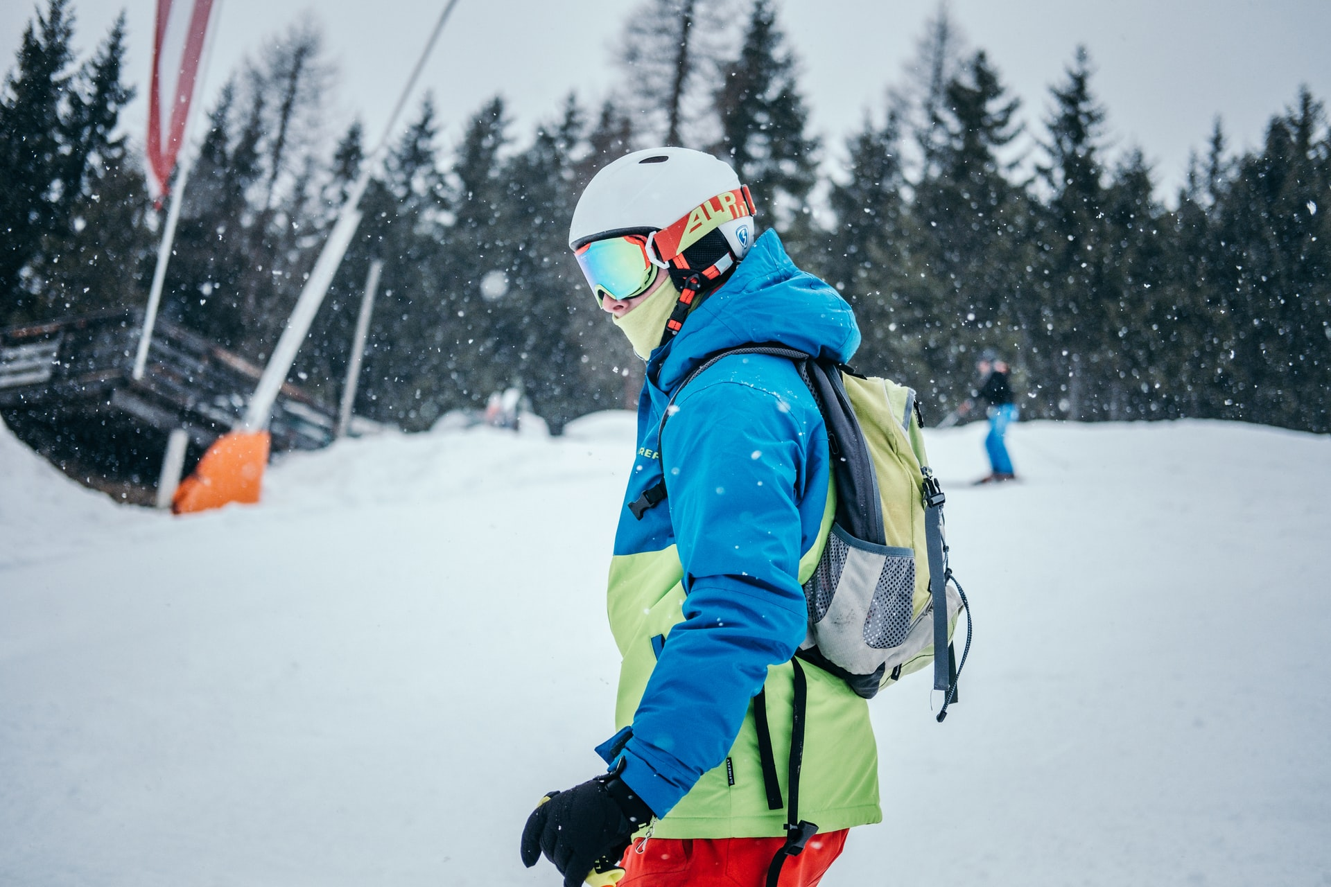 person-in-ski-gear-standing-in-snow-in-front-of-forest-up-a-mountain-skiing-ski-season-packing-list
