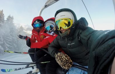 three-women-female-friends-sat-on-ski-lift-going-up-a-mountain-in-ski-gear-with-snow-in-background-ski-season-packing-list