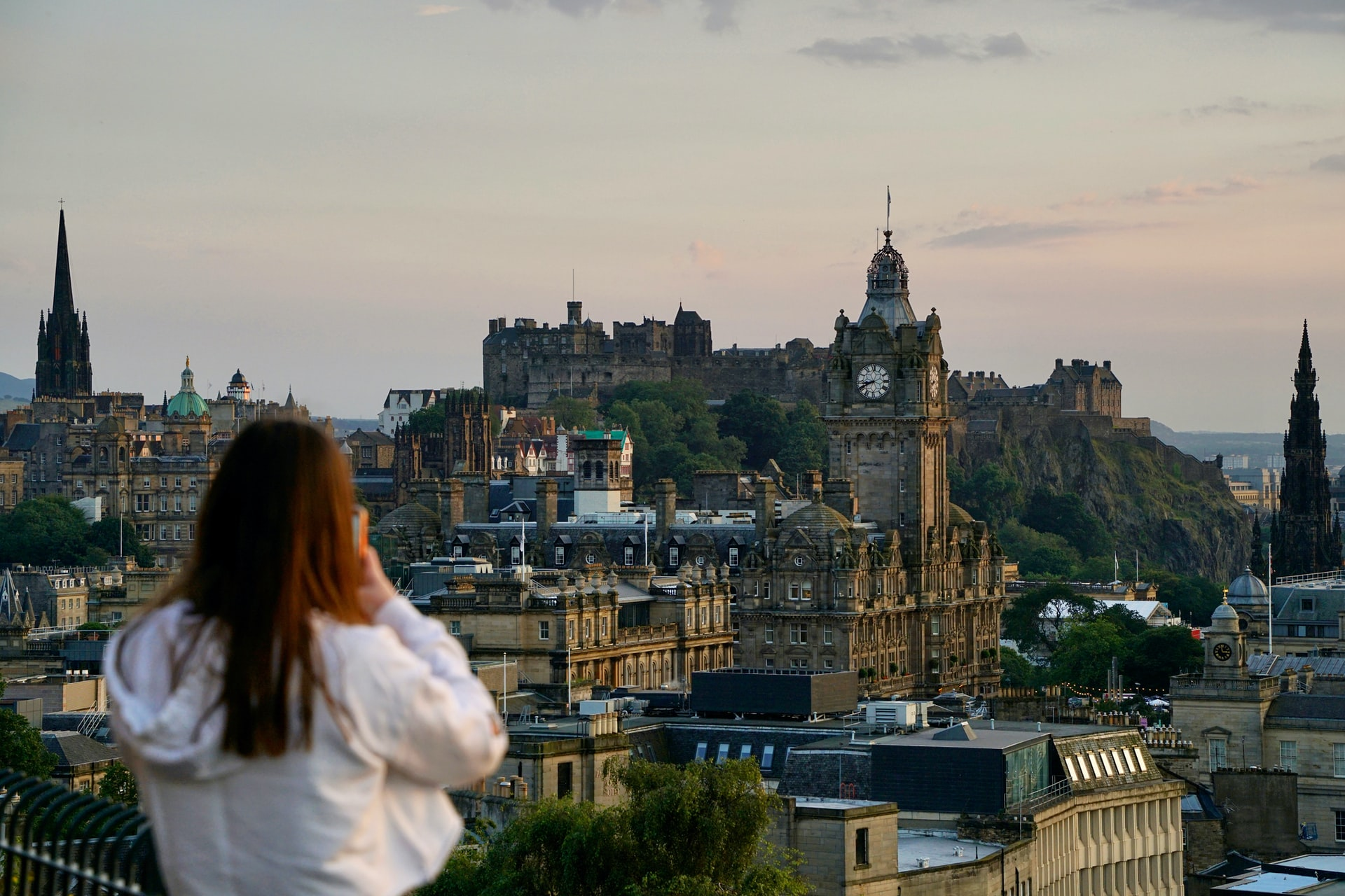 young-woman-taking-photo-of-old-historic-city-from-hill-viewpoint-at-sunset-calton-hill-free-things-to-do-in-edinburgh