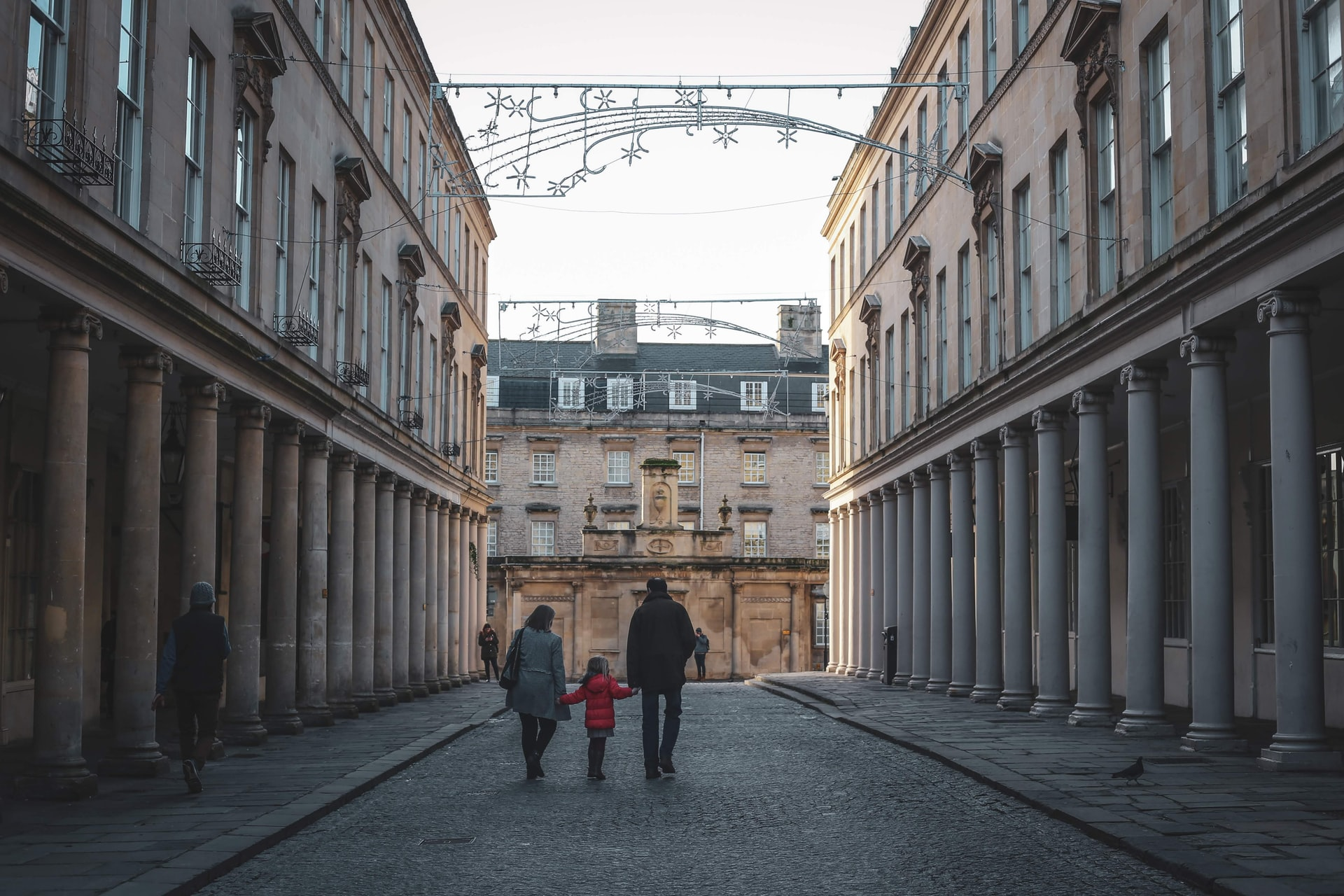 couple-with-young-child-walking-down-old-historic-street-in-bath-at-christmas