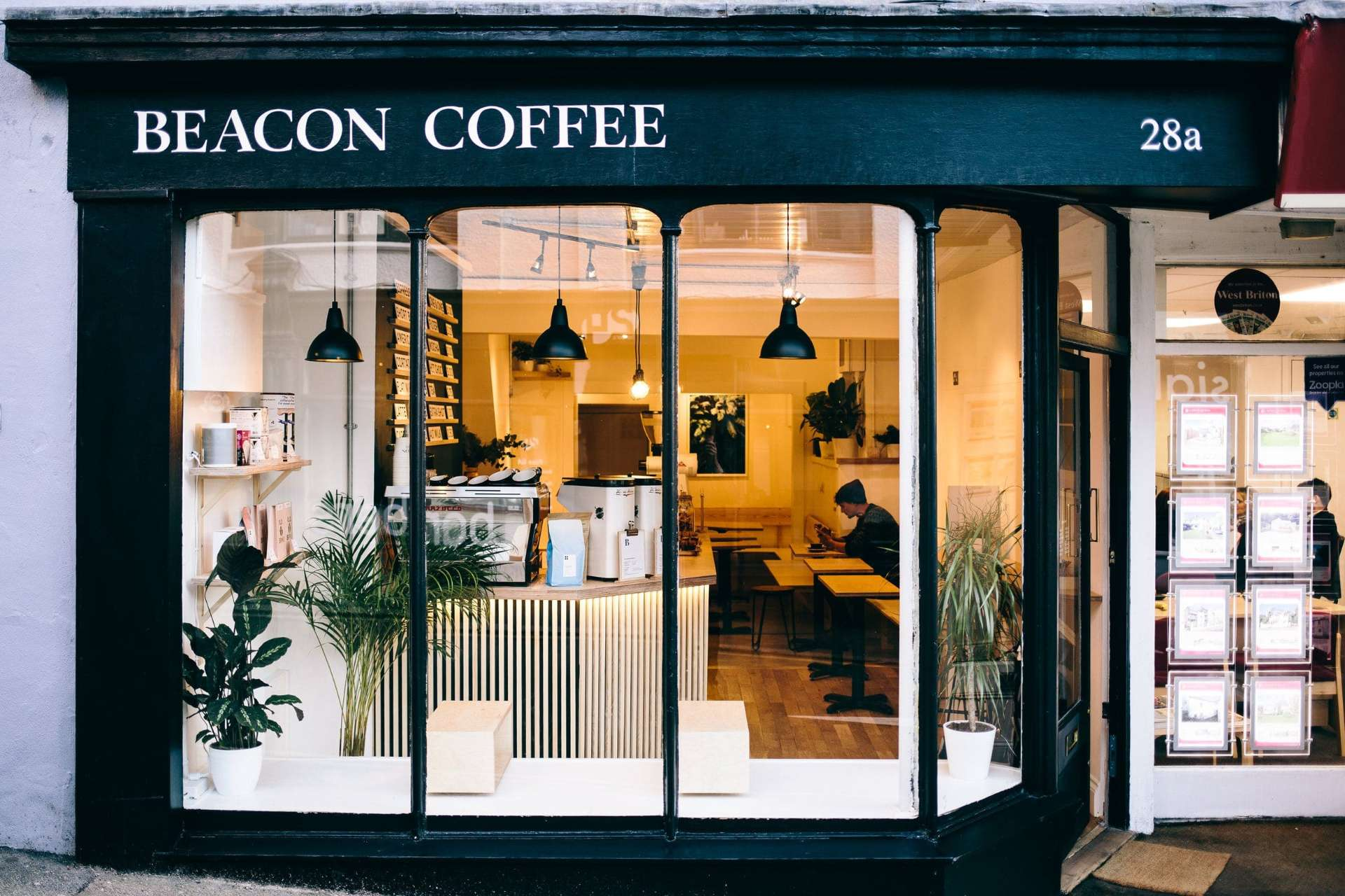 exterior-of-coffee-shop-with-man-working-at-laptop-at-table-beacon-coffee-places-to-eat-in-falmouth