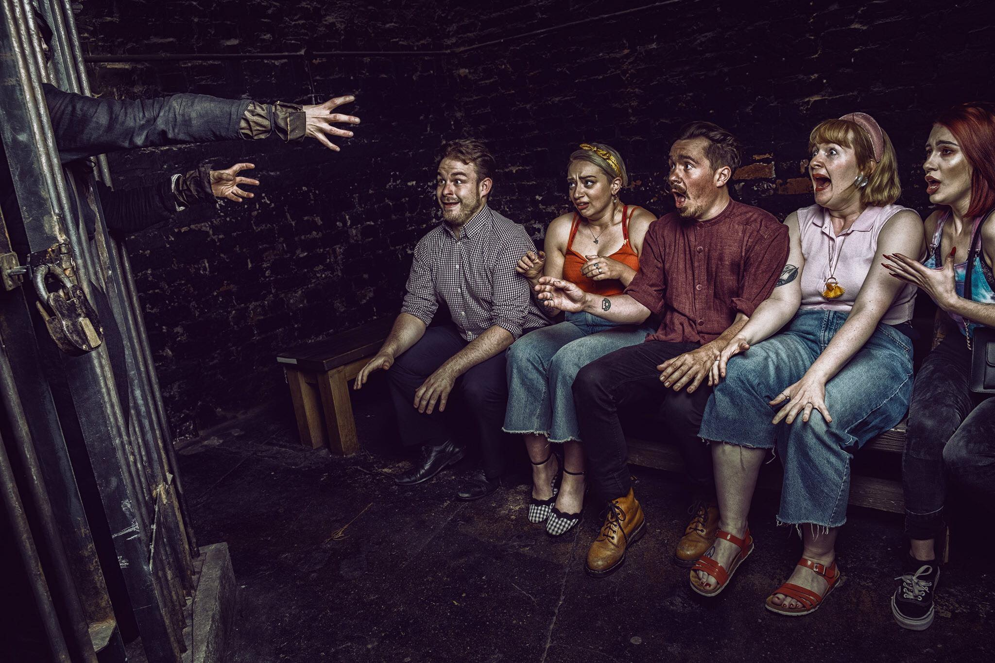 five-young-people-scared-at-hand-in-darkness-at-york-dungeon
