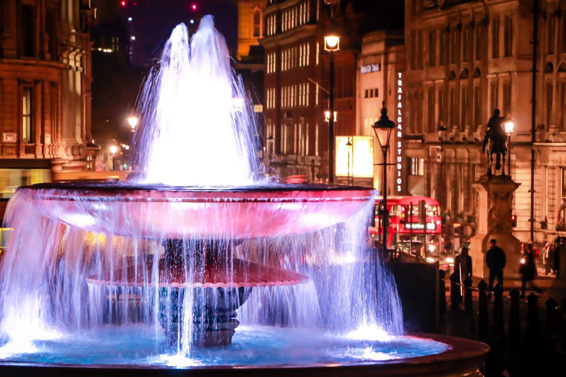 fountain-in-trafalgar-square-at-night-lit-up-by-lights