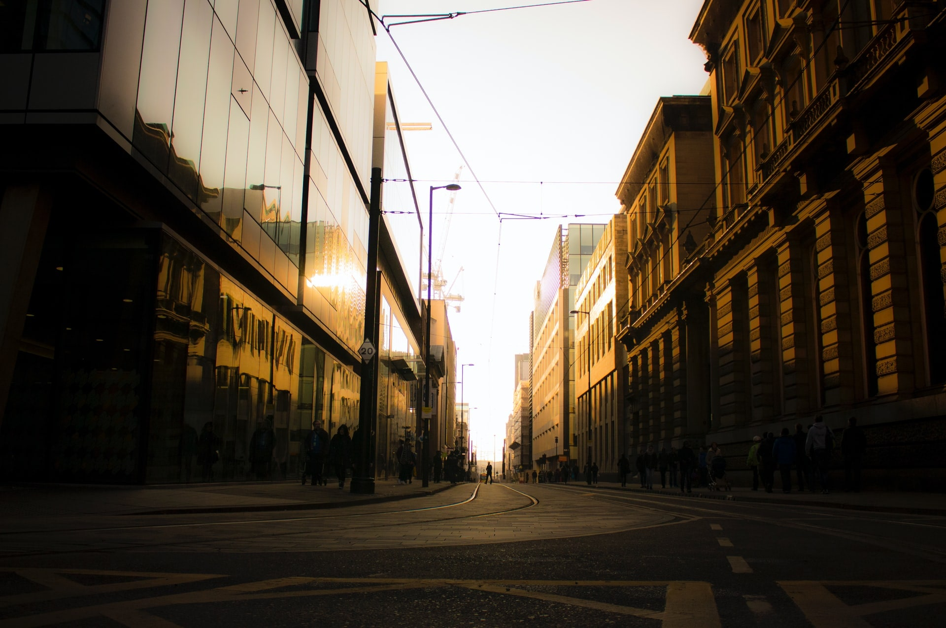 golden-light-shining-through-city-street-on-tramlines-at-sunset-in-manchester