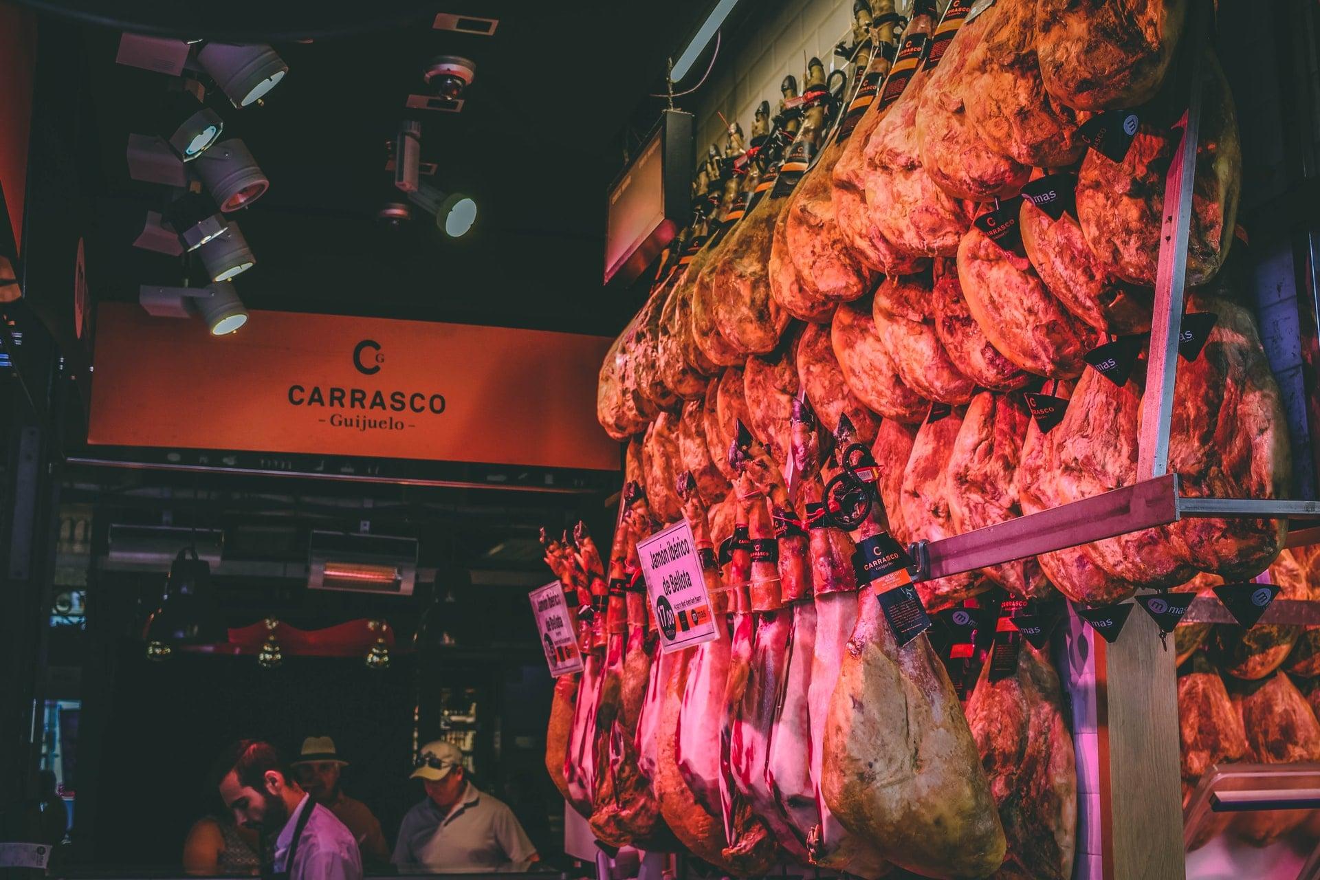 ham-hanging-up-in-market-at-night-carrasco-guijuelo-mercado-de-san-miguel