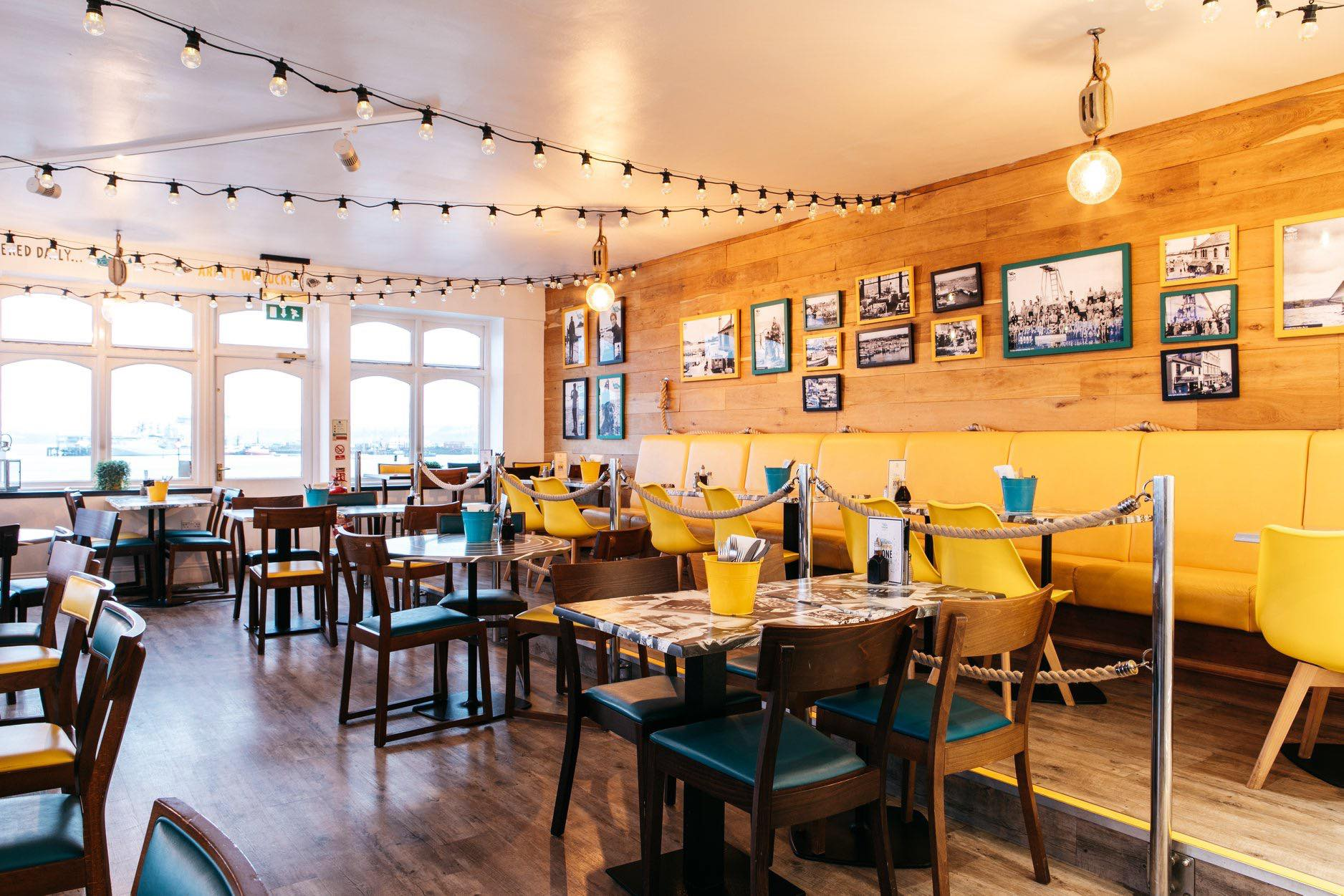 interior-of-fancy-fish-and-chip-shop-with-yellow-and-teal-tables-and-chairs-harbour-lights-places-to-eat-in-falmouth
