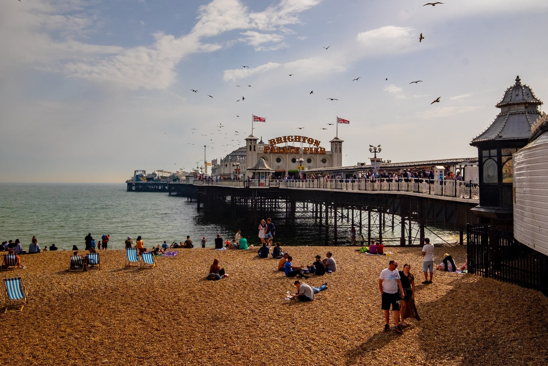people-lounging-on-pebble-beach-by-the-seaside-beside-brighton-pier-while-seagulls-fly-overhead-best-uk-city-breaks-for-couples