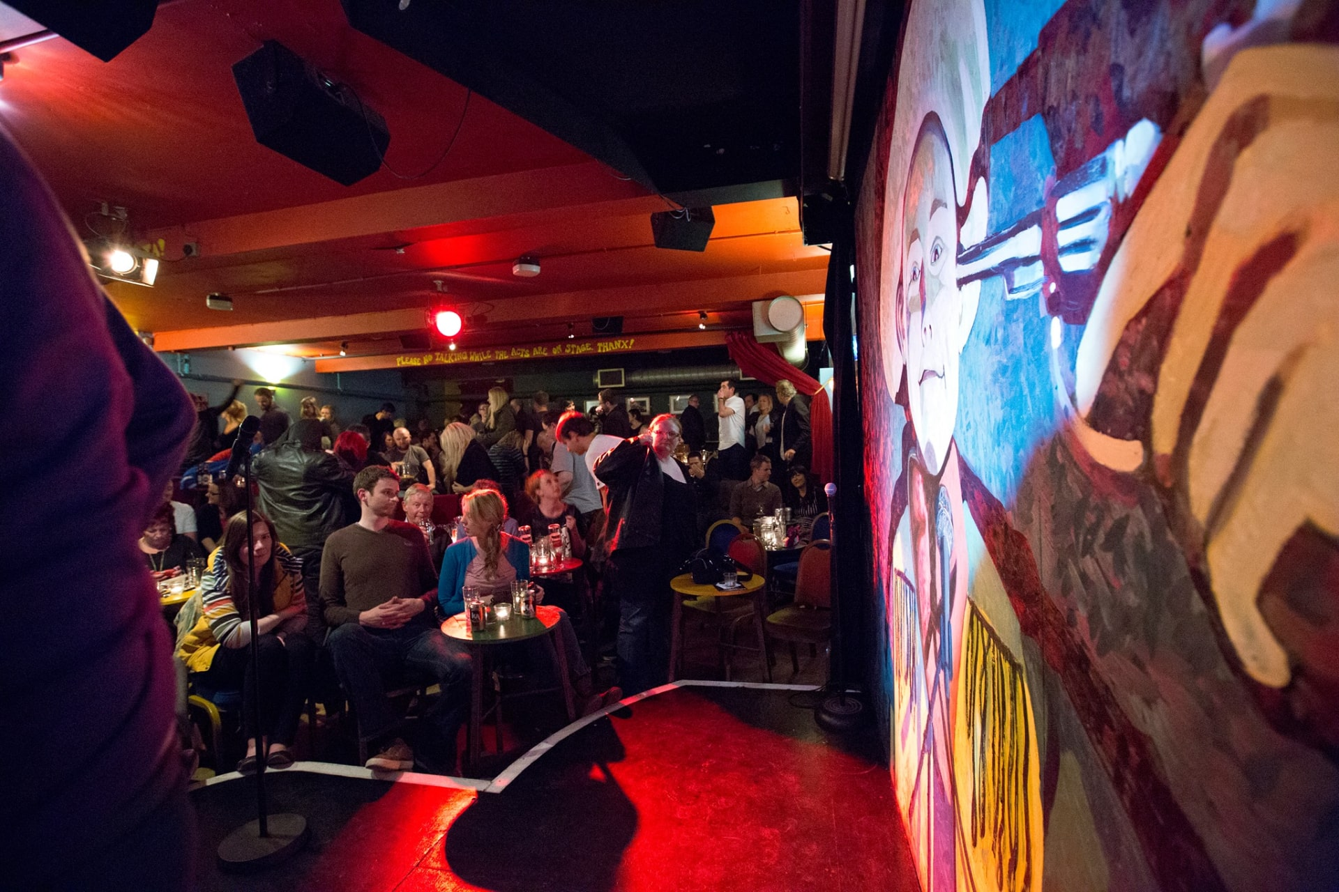 people-sitting-at-tables-and-standing-waiting-to-watch-a-comedy-gig-at-the-stand-glasgow