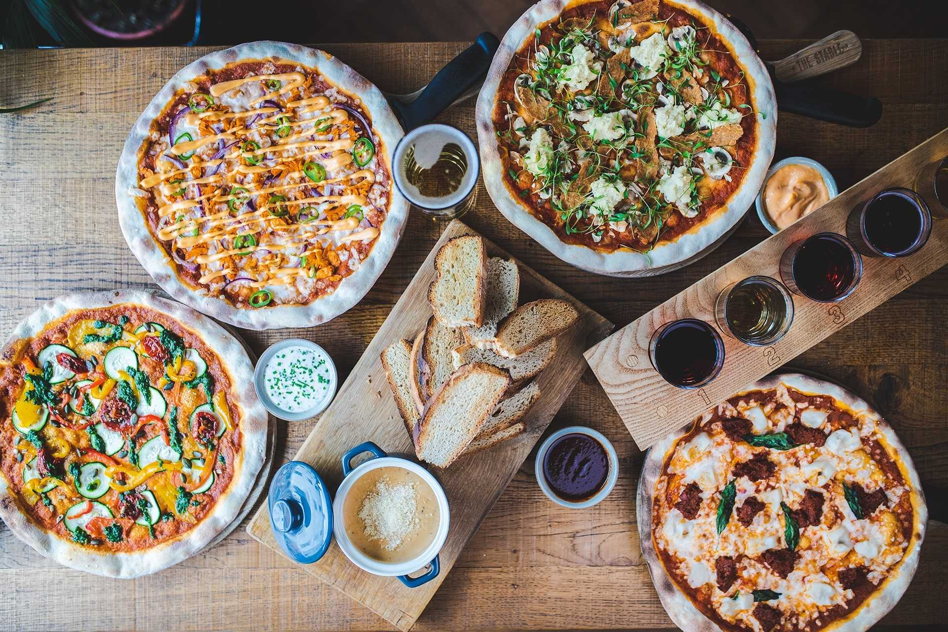 plates-of-pizza-and-bread-on-table-at-the-stable-places-to-eat-in-falmouth