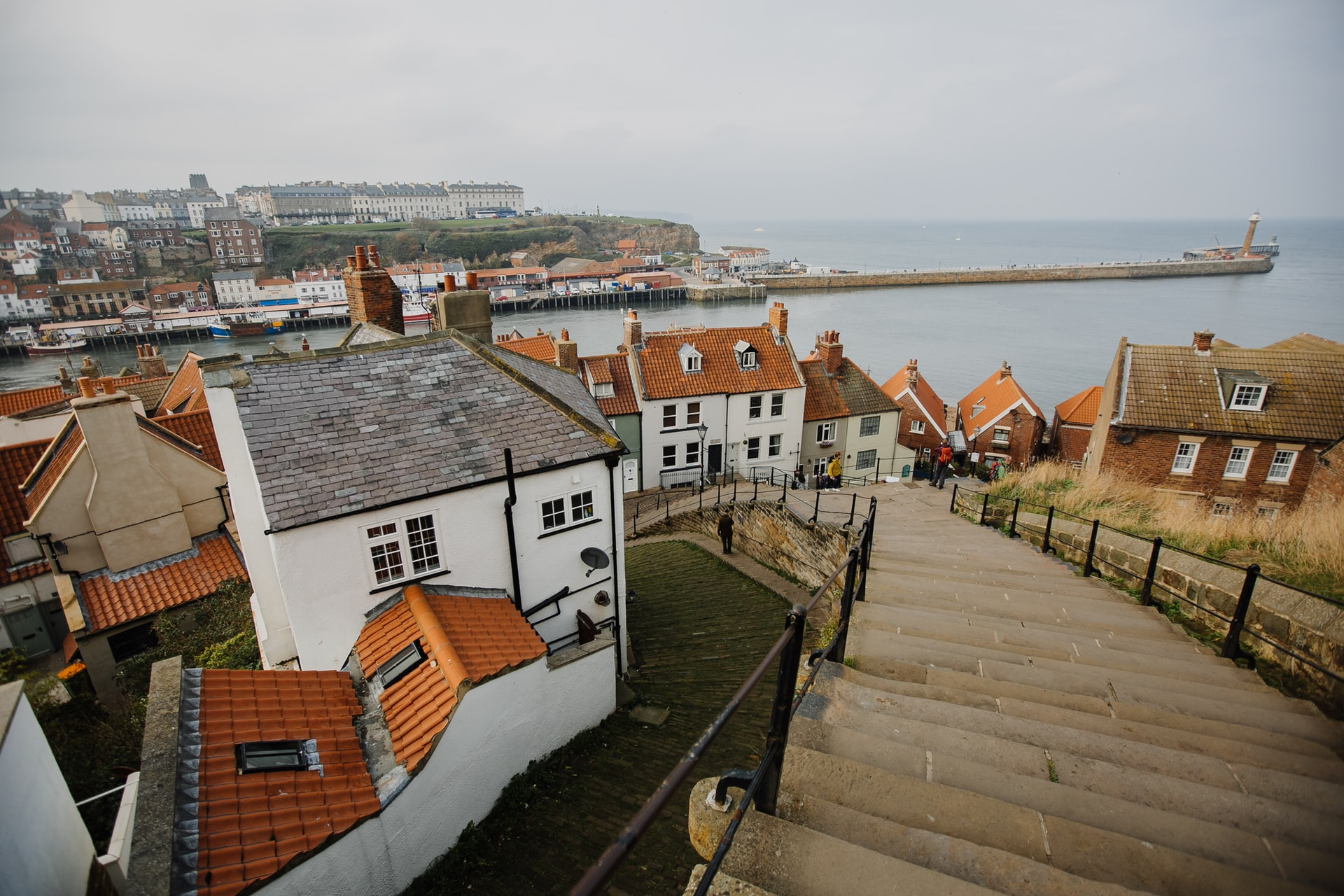 steps-heading-down-to-harbour-with-orange-roofed-houses-in-whitby