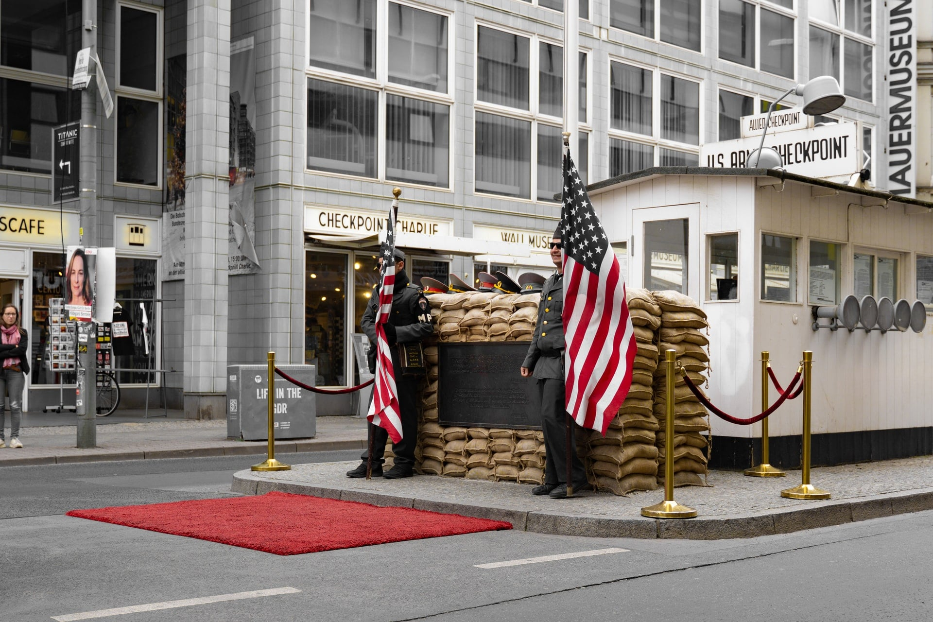 two-army-officers-standing-with-us-flags-in-the-middle-of-a-city-road-checkpoint-charlie