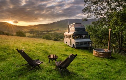 a-converted-bus-with-a-vw-camper-bedroom-on-the-roof-in-a-remote-corner-of-a-field-with-hot-tub-and-mountains-in-background-hinterlandes-glamping-with-hot-tub-lake-district