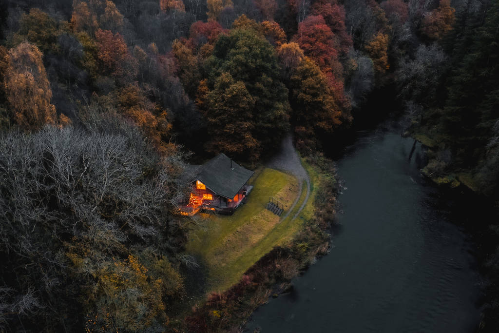 black-cabin-lodge-on-edge-of-a-lake-in-dark-at-night-in-autumn-at-edenhall-estate-in-cumbria