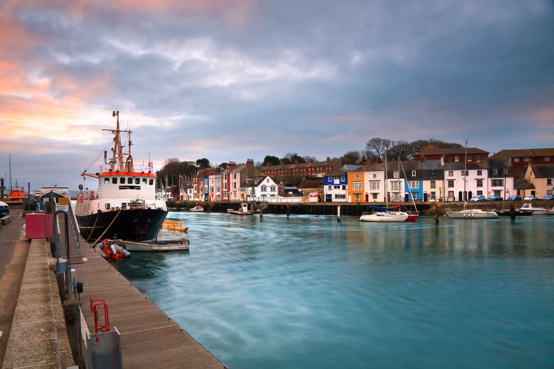 boats-on-deck-at-weymouth-harbour-by-colourful-houses