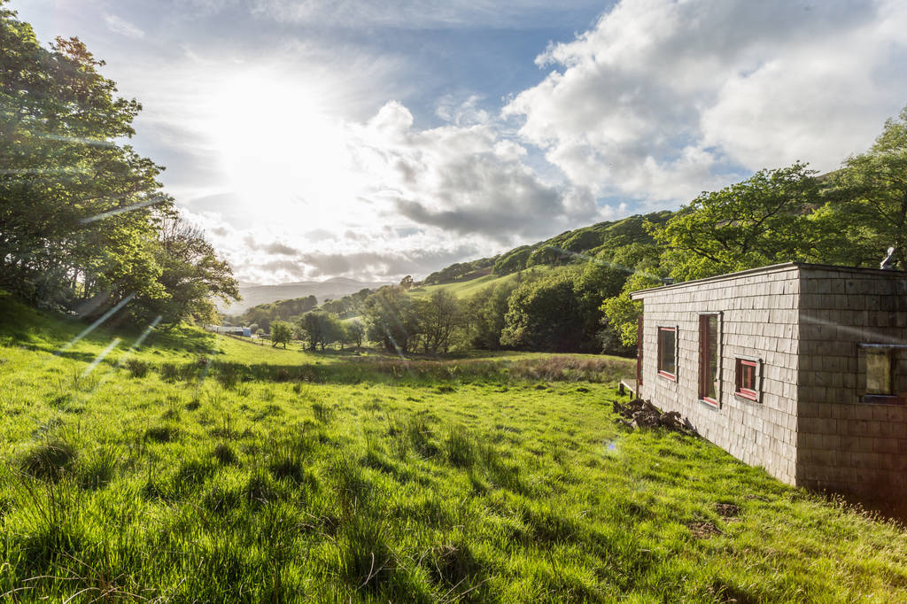 cabin-in-green-field-on-sunny-day-caban-coch-at-beudy-banc-glamping-snowdonia
