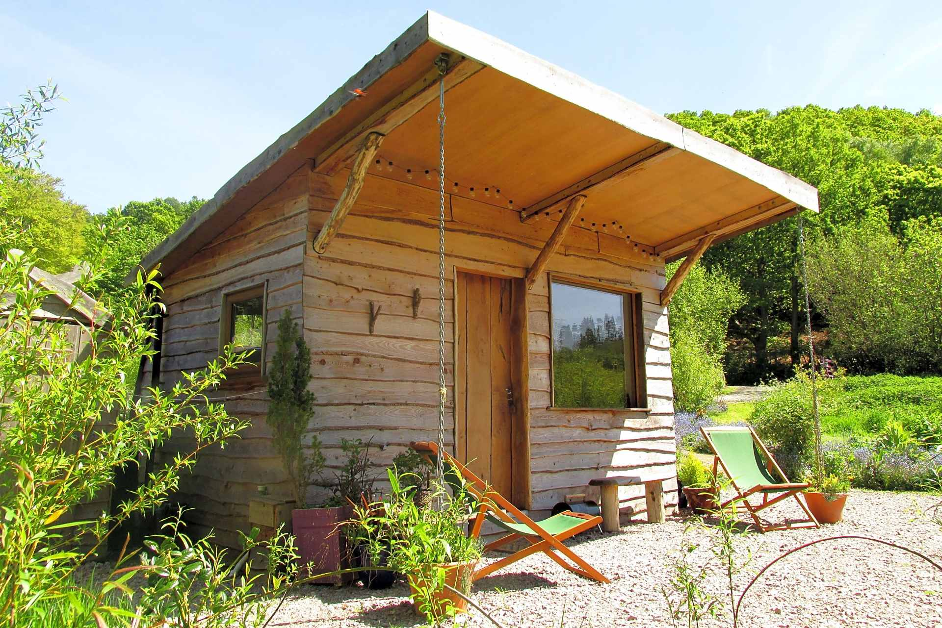 cabin-with-deckchairs-on-stones-outside-in-garden-the-cabins-conwy