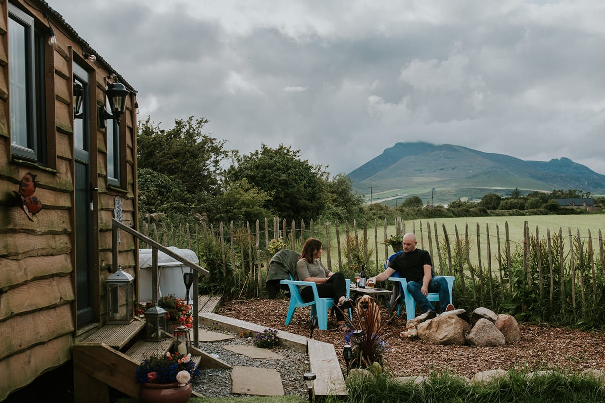 couple-sitting-outside-on-chairs-by-willowtree-shepherds-hut-with-a-mountain-in-background-glamping-northern-ireland