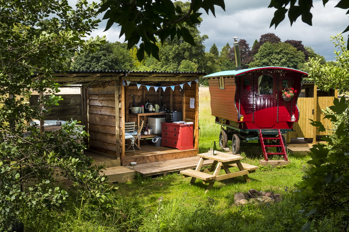 evelyn-gypsy-caravan-red-wagon-in-field-with-hot-tub-and-outdoor-kitchen-armathwaite