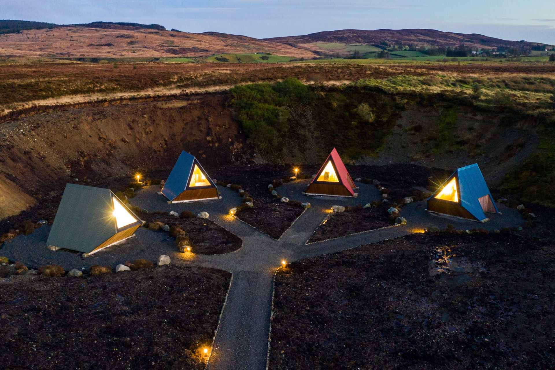 four-deserted-pods-lit-up-at-night-sperrin-view-glamping