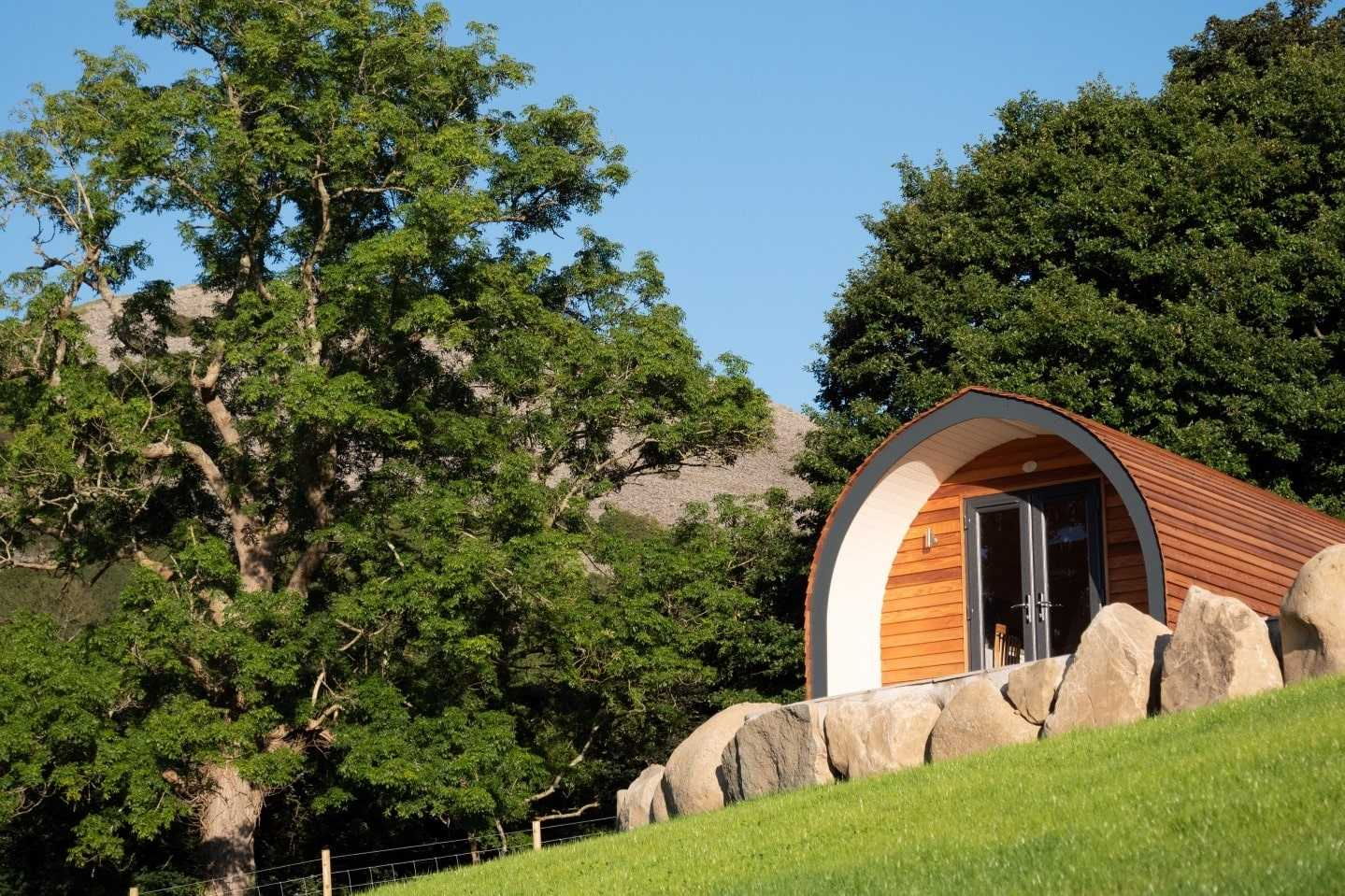 glamping-pod-at-top-of-green-field-with-mountain-in-background-three-streams-glamping