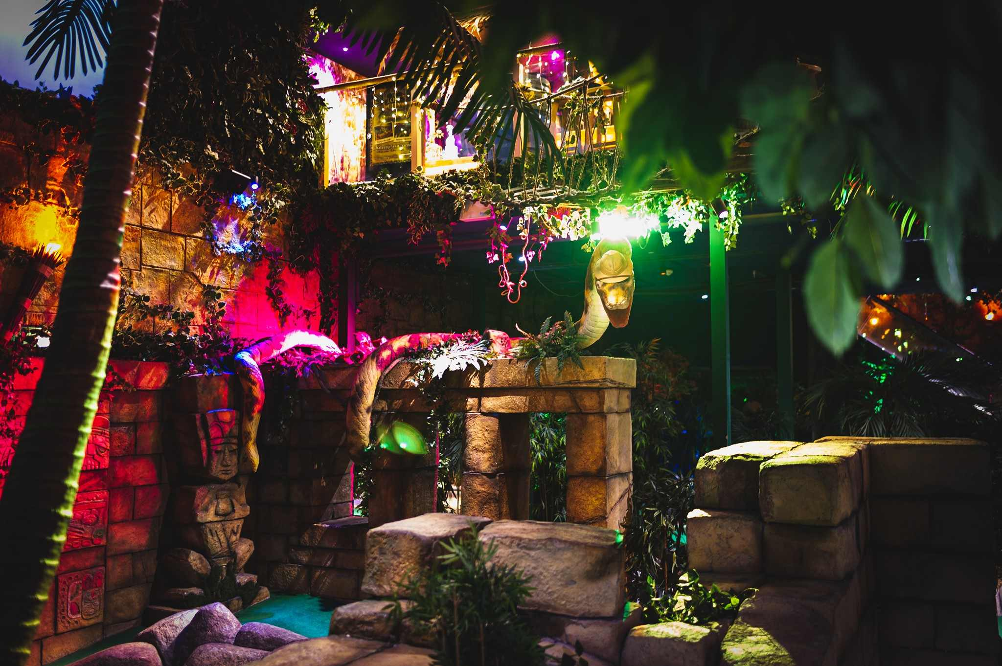 indoor-jungle-scene-lit-up-by-colourful-lights-at-the-lost-city-adventure-golf-indoor-activities-nottingham