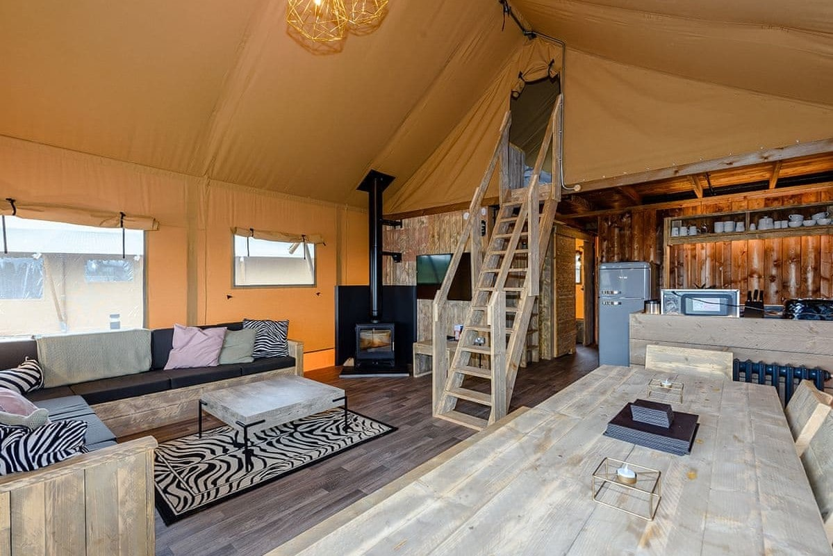 interior-of-safari-tent-with-woodburner-kitchen-and-lounge-area-and-steps-leading-up-to-second-floor-ullswater-heights-safari-tent