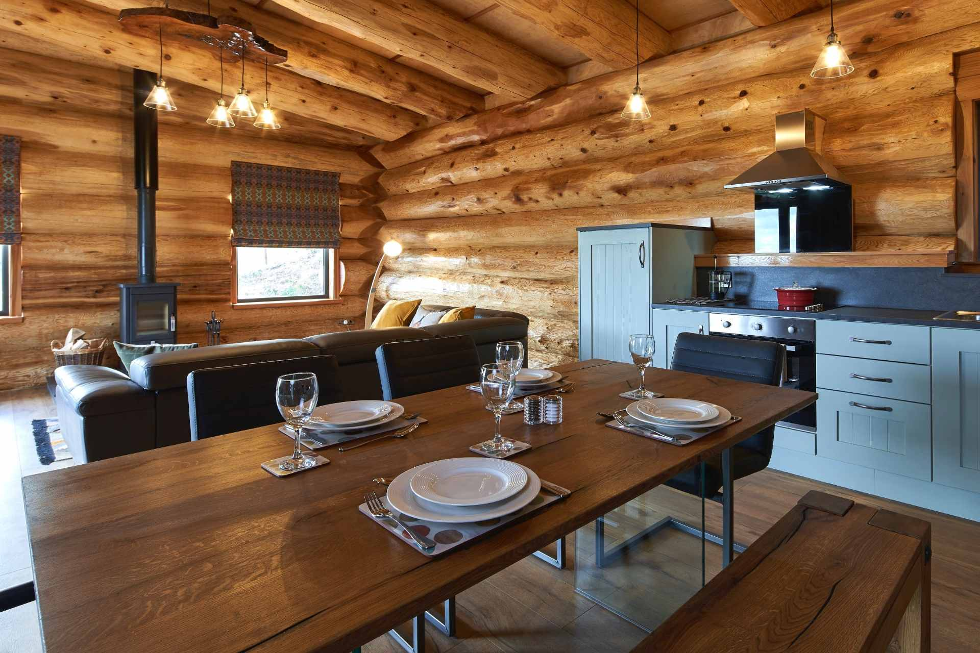 kitchen-dining-table-sofas-and-logburner-in-aurora-salix-cabin