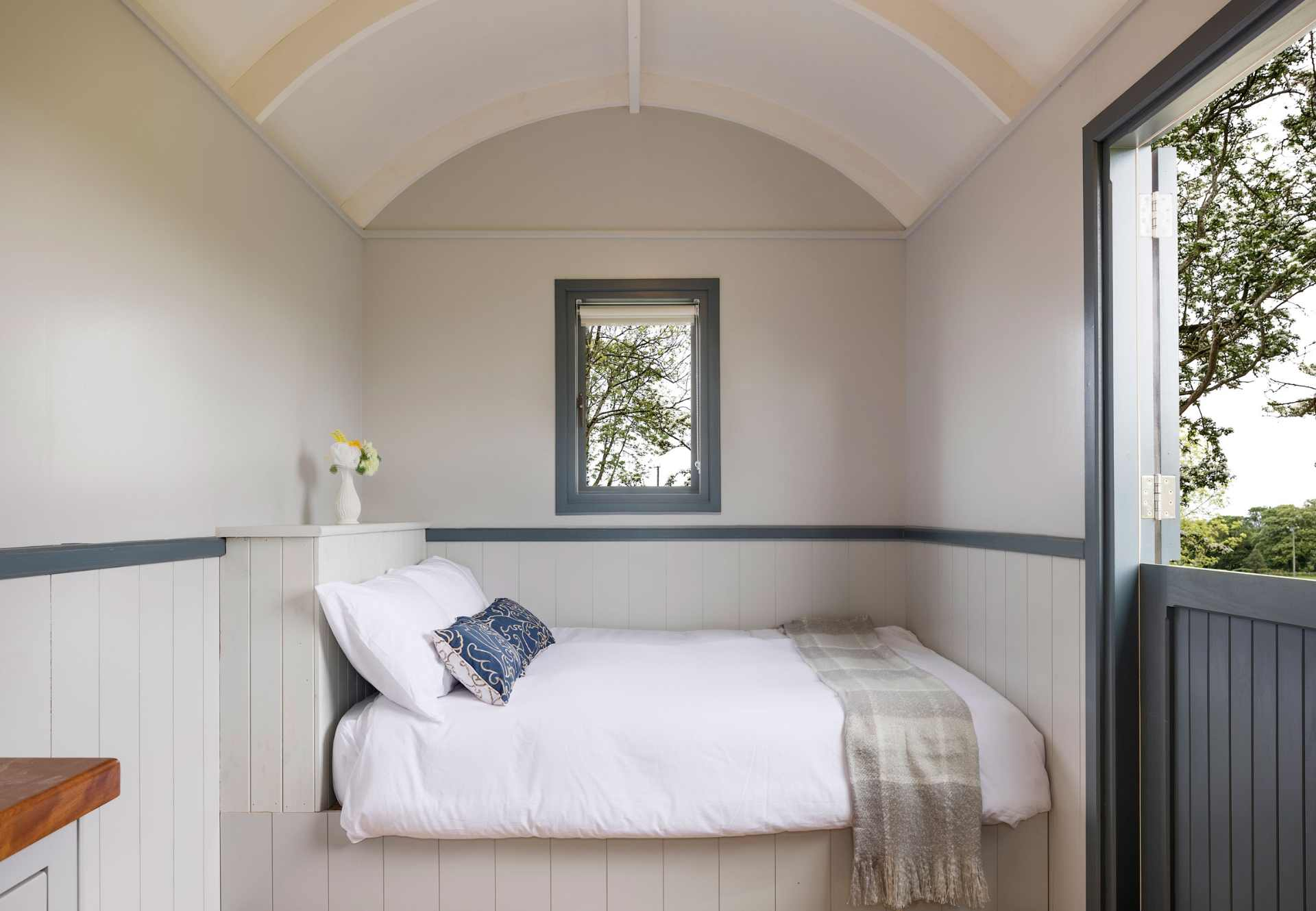 minimalist-white-bed-in-snowdrop-shepherds-hut-at-oakwell-holiday-village