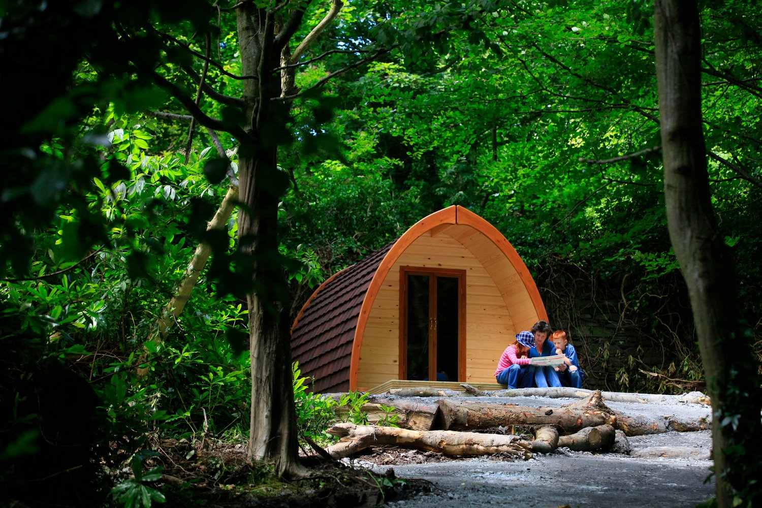 mum-and-two-kids-sitting-on-floor-outside-glamping-pod-in-woodland-castle-ward-pods