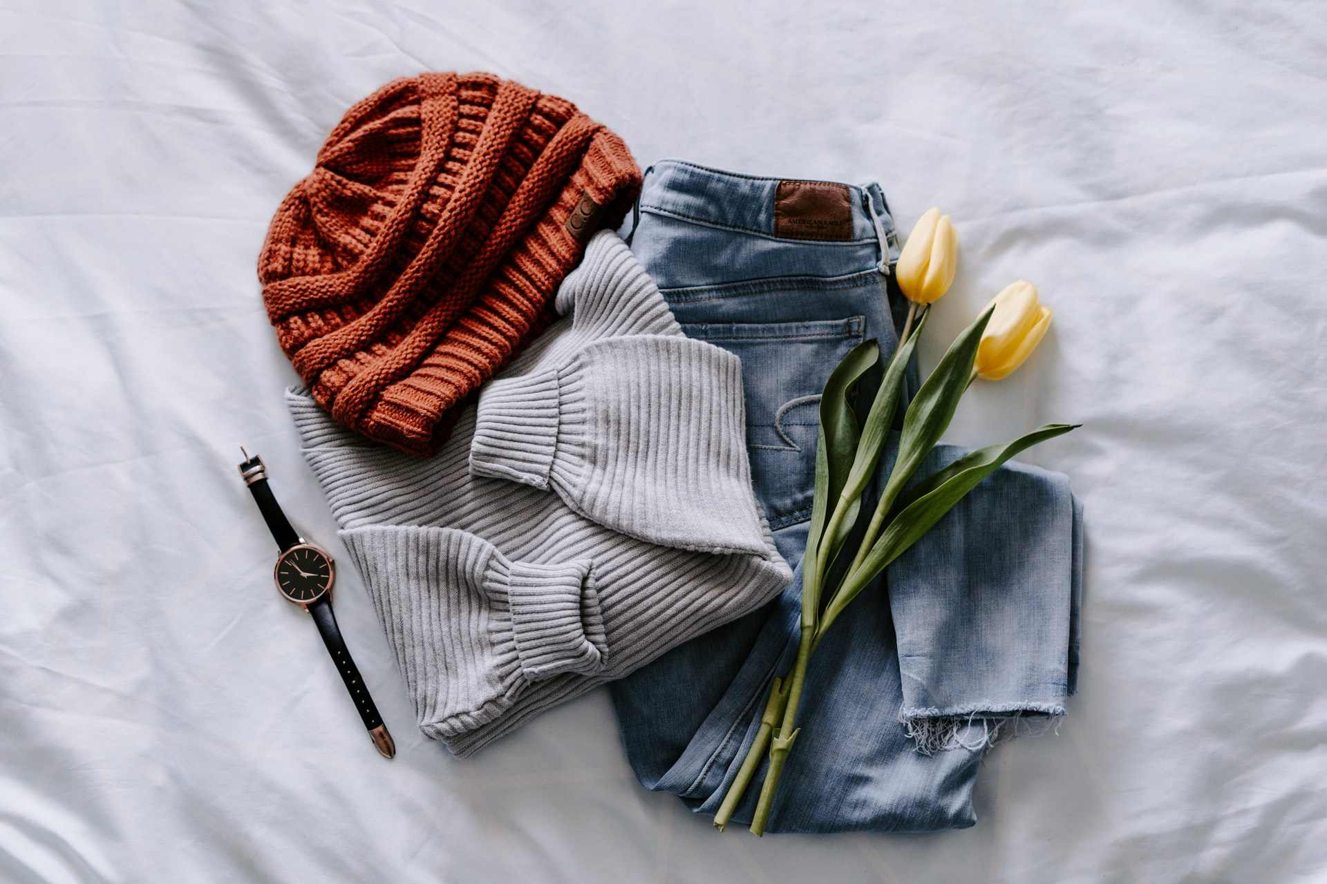 orange-knit-beanie-grey-jumper-blue-pair-of-jeans-and-watch-on-white-bed-travel-capsule-wardrobe