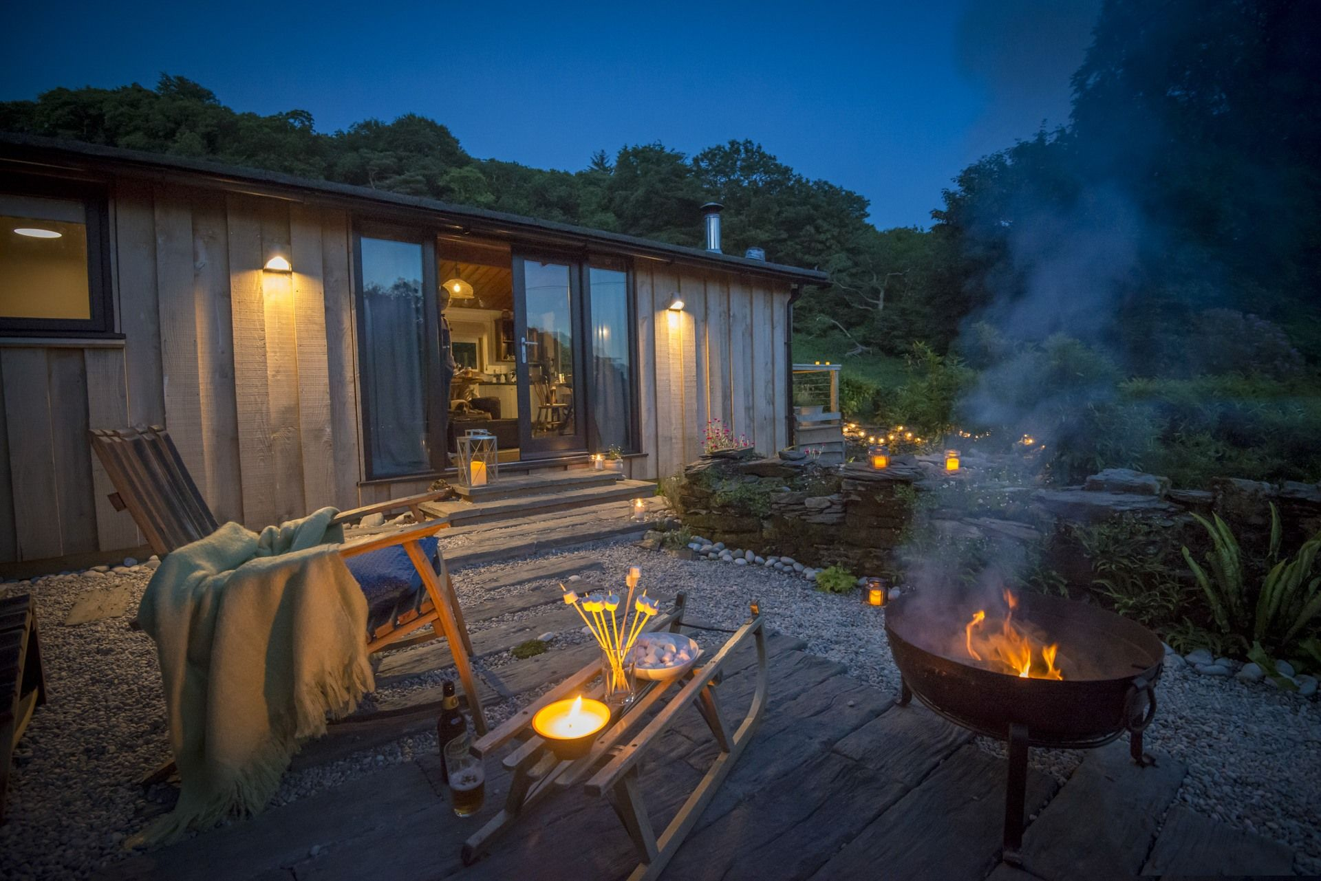 outside-little-kestrel-wood-cabin-at-night-with-fire-and-rocking-chair-in-aberdovey