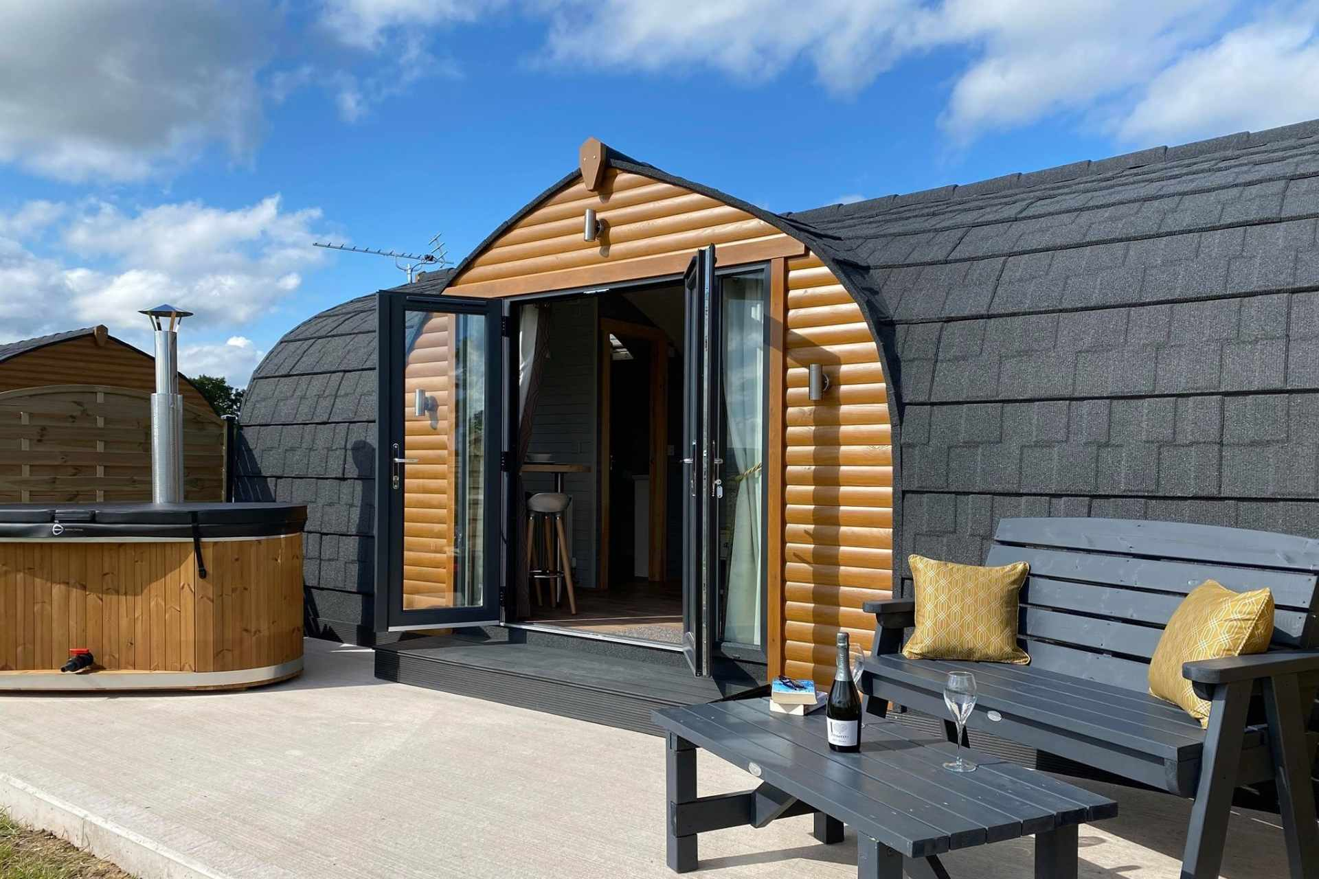 pasturewood-holiday-pods-on-decking-with-bench-and-table-on-summers-day-glamping-with-hot-tub-lake-district