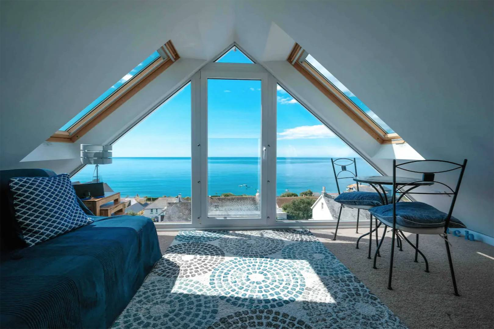 triangular-living-room-with-views-out-to-blue-sea-in-coastal-studio-loft-apartment-in-downderry