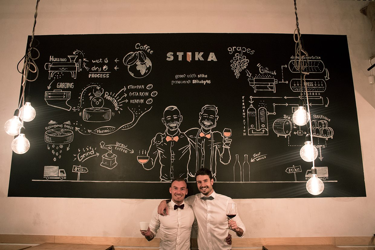 two-waiters-holding-a-glass-of-wine-and-mug-of-coffee-against-blackboard-in-stika