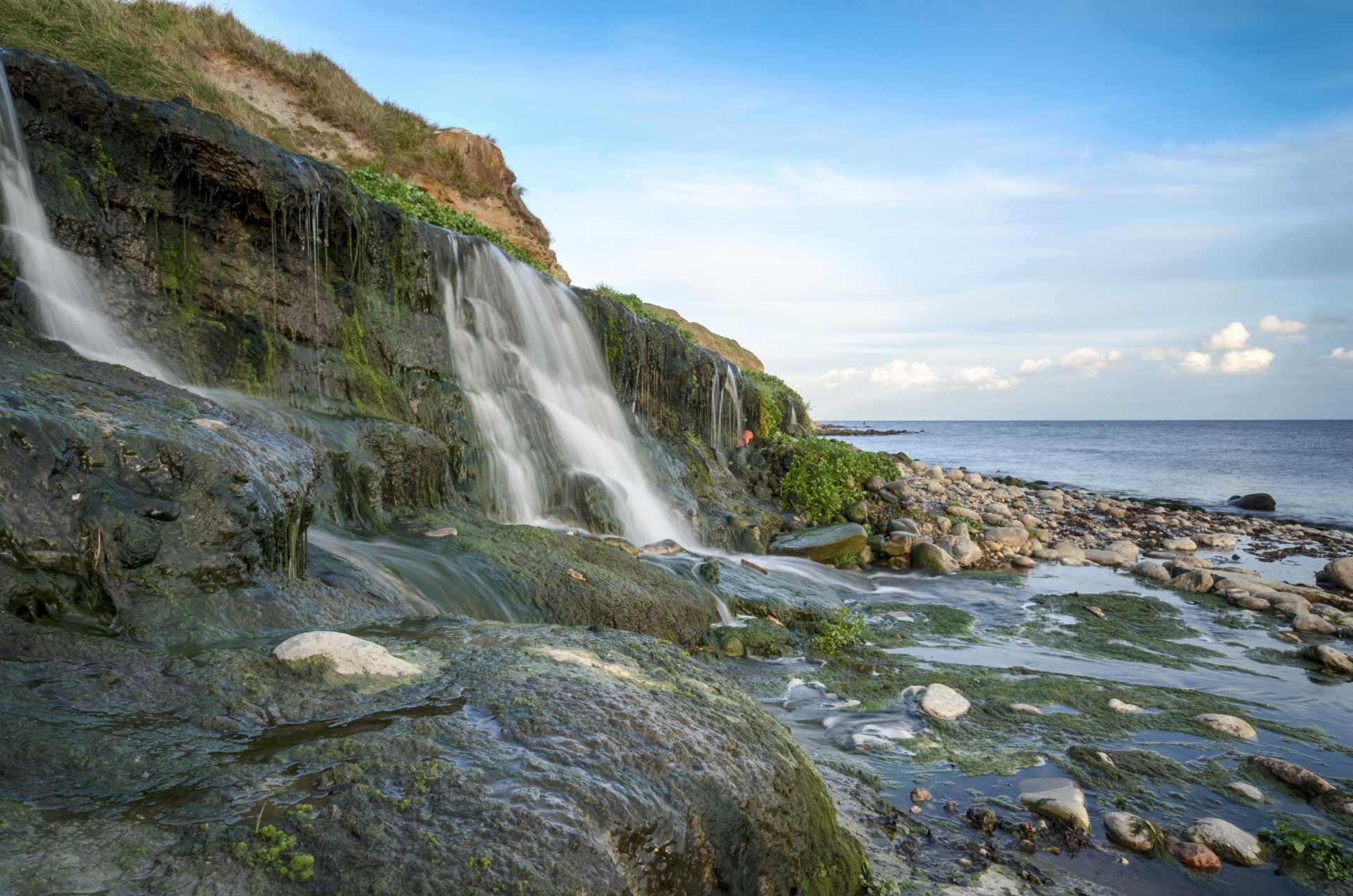 waterfall-going-onto-stony-osmington-mills-beach-best-beaches-in-dorset