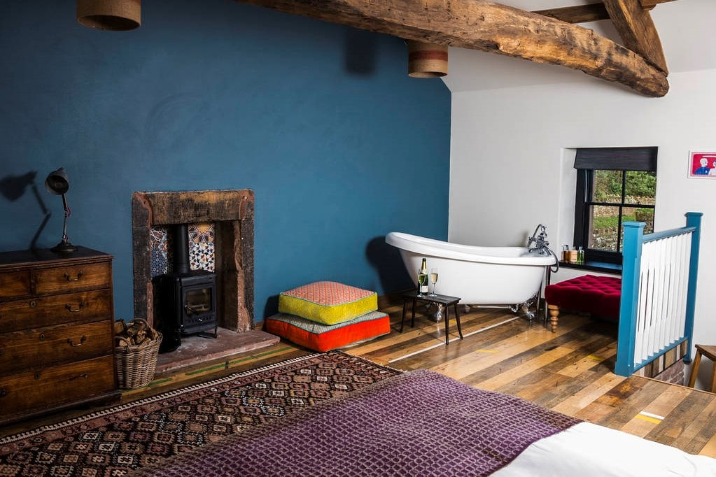 white-roll-top-bath-woodburner-chest-of-drawers-and-bed-in-bedroom-of-the-bothy-at-high-barn-edenhill-estate
