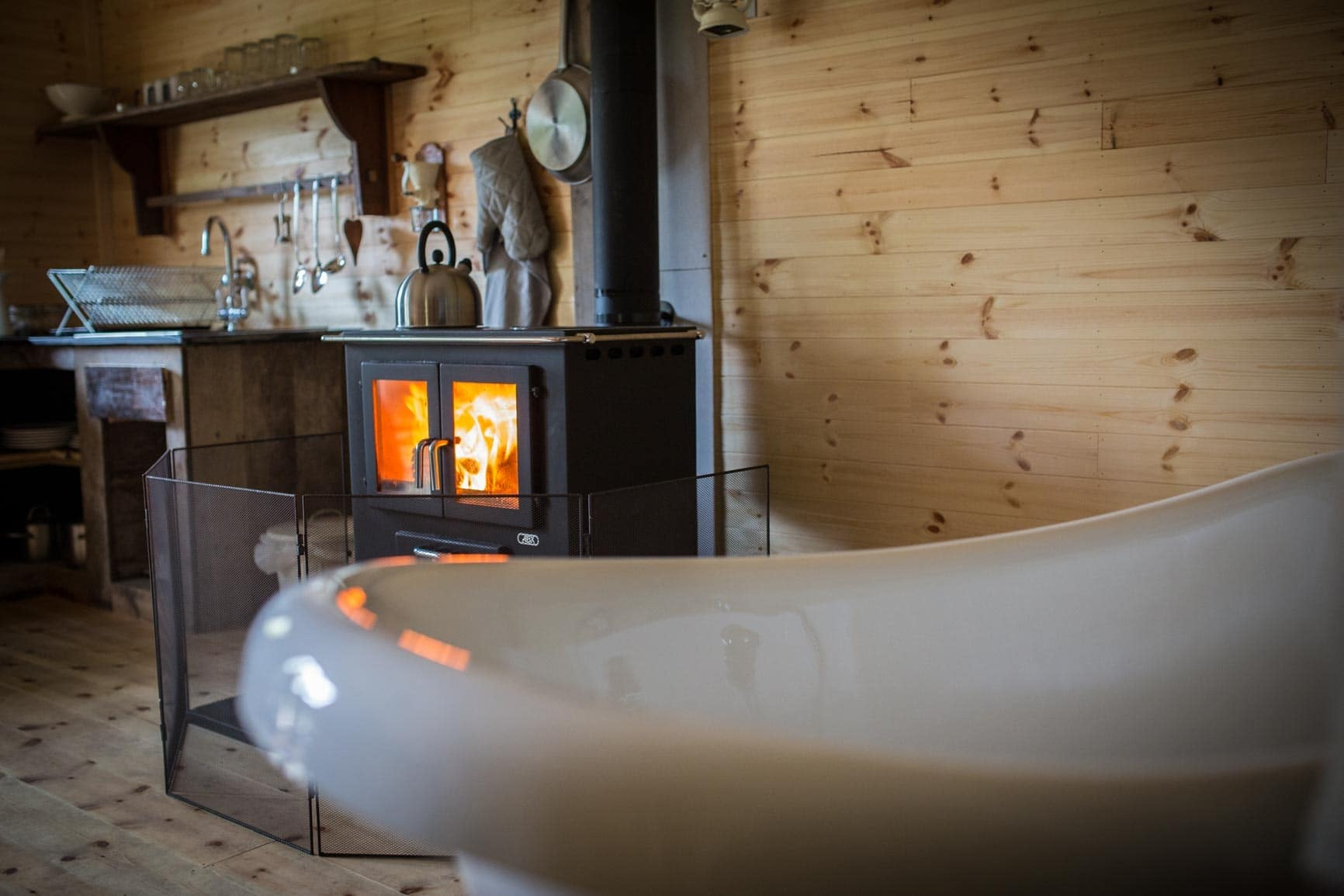 white-roll-top-freestanding-bath-tub-by-woodburner-in-riverside-glamping-tented-lodges