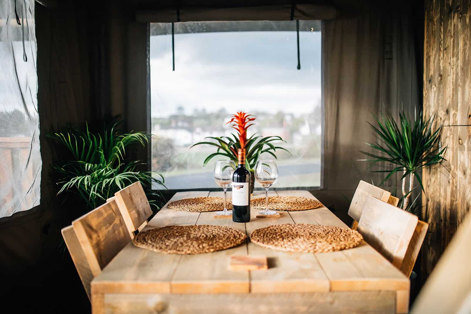 wooden-table-with-a-bottle-of-red-wine-inside-lets-go-hydro-safari-tent