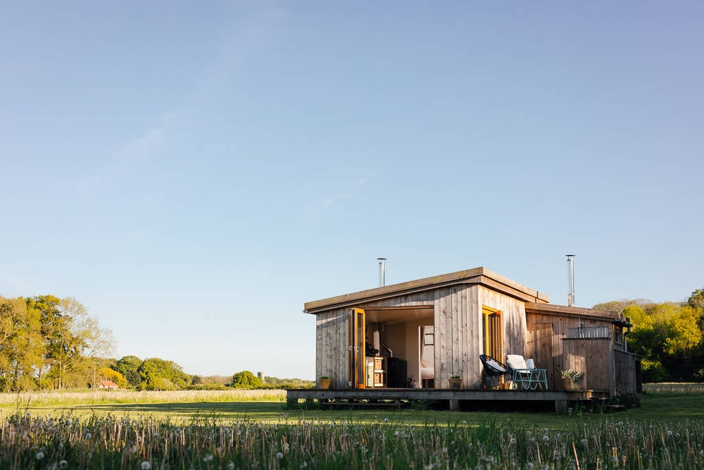a-sunny-view-of-woodcock-cabin-in-field-at-bagthorpe-farm-glamping-norfolk