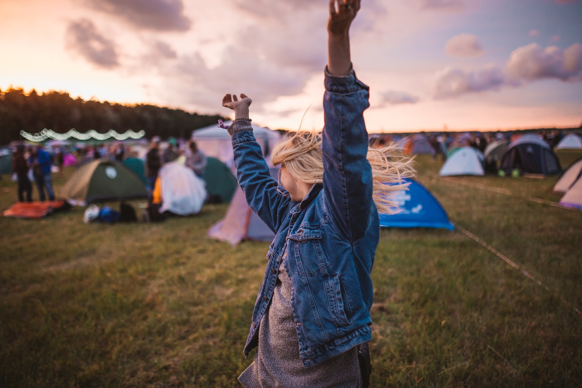 blonde-woman-in-denim-jacket-dancing-in-field-of-tents-at-festival-packing-list-for-festival