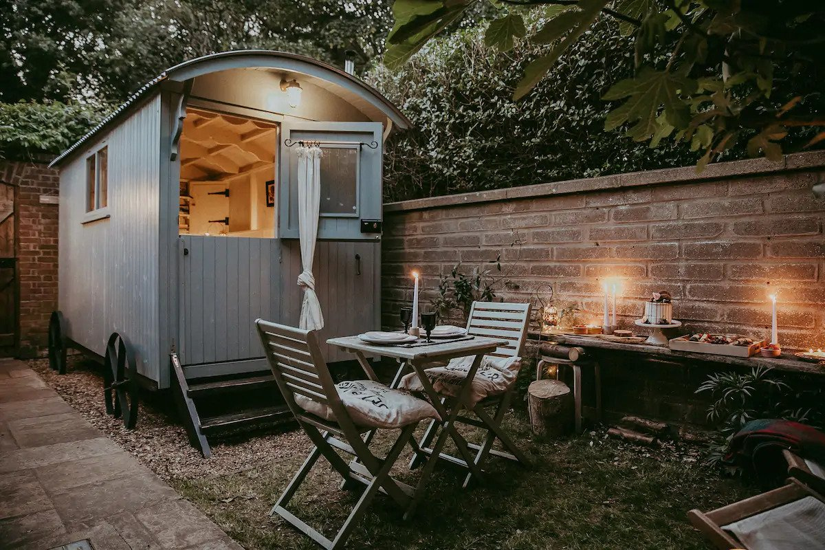 blue-the-good-shepherds-hut-with-table-and-chairs-at-night-in-garden